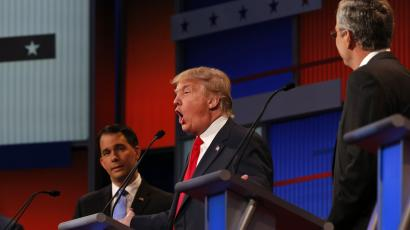Donald Trump answers a question as fellow candidates Wisconsin Governor Scott Walker (L) and former Florida Governor Jeb Bush (R) listen at the first official Republican presidential candidates debate of the 2016 U.S. presidential campaign
