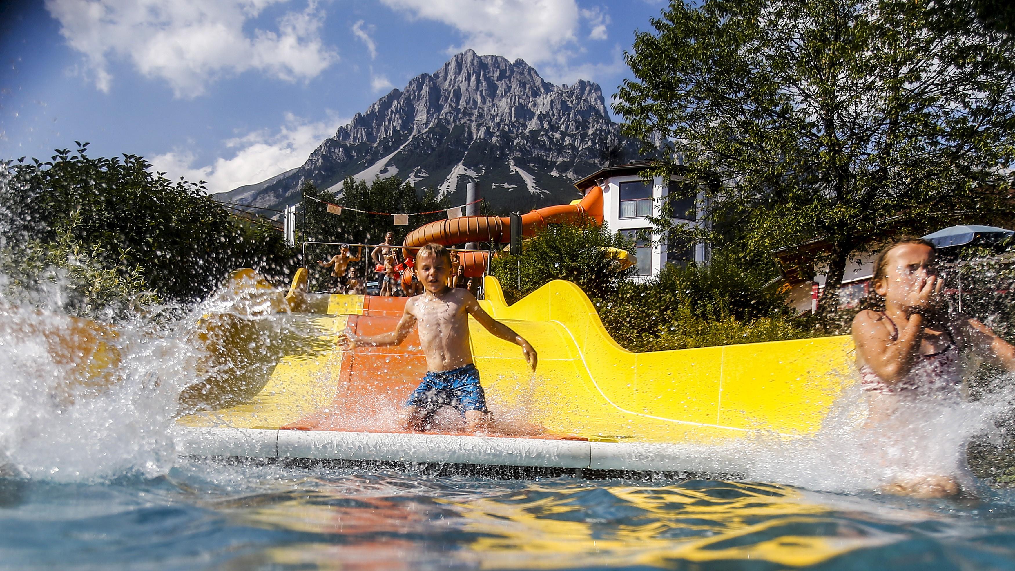 Children slide down a water slide on a hot summer day in the western Austrian village of Ellmau.