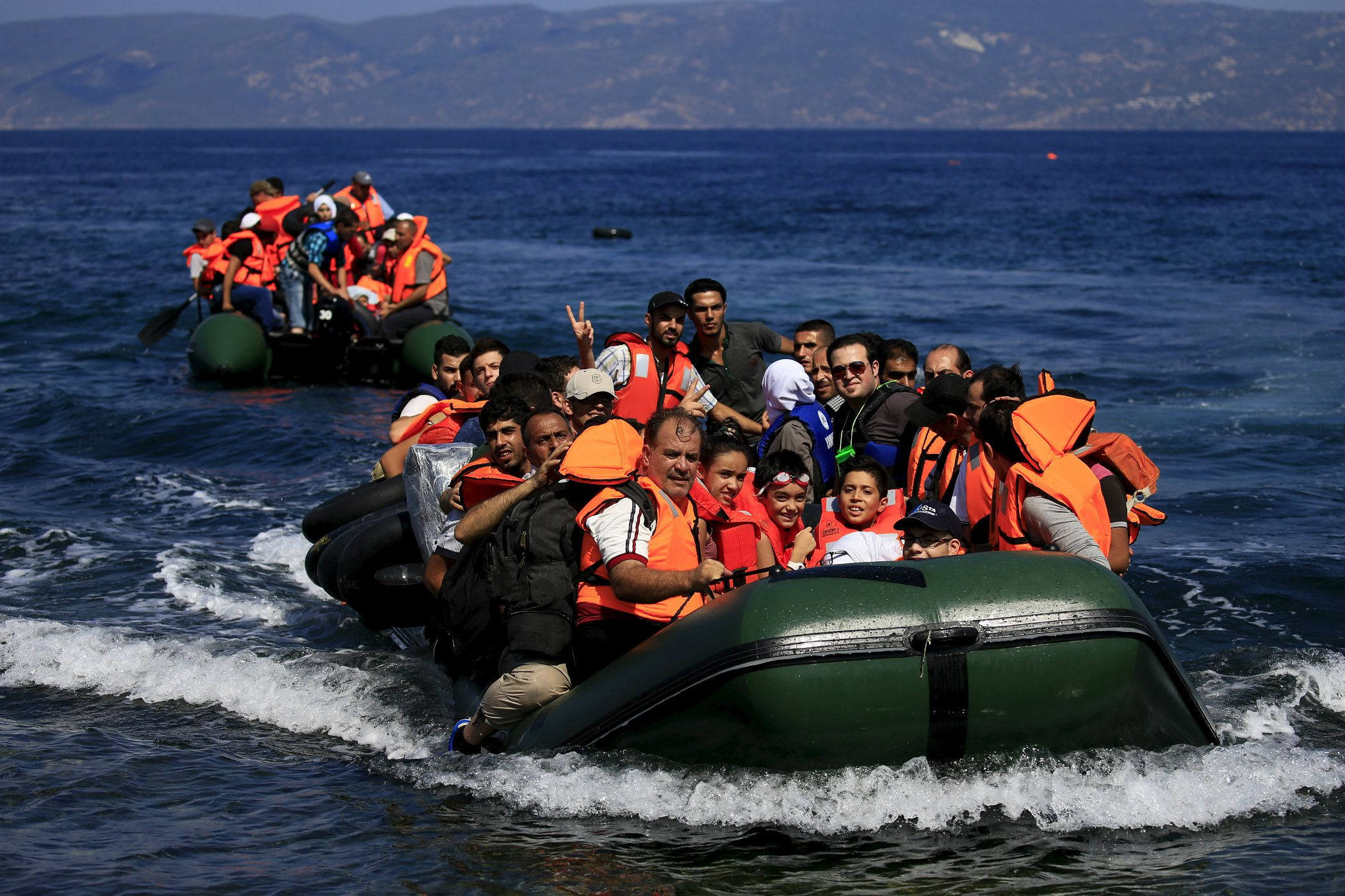 DATE IMPORTED:August 22, 2015Syrian refugees arrive on two dinghies on the island of Lesbos, Greece August 22, 2015. Greece ferried hundreds of refugees to its mainland on Friday to relieve the pressure on outlying islands that have been overwhelmed by thousands of people arriving by boat to flee Syria's civil war. REUTERS/Alkis Konstantinidis