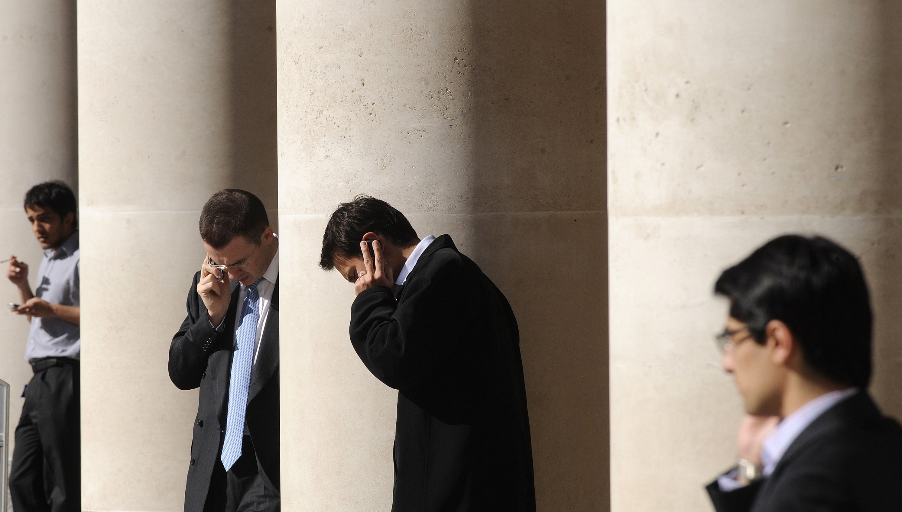 City workers make phone calls outside the London Stock Exchange in Paternoster Square in the City of London at lunchtime October 1, 2008. European policymakers have called on the U.S. Senate to approve a revised rescue plan aimed at tackling the worst financial crisis since the 1930s. REUTERS/Toby Melville