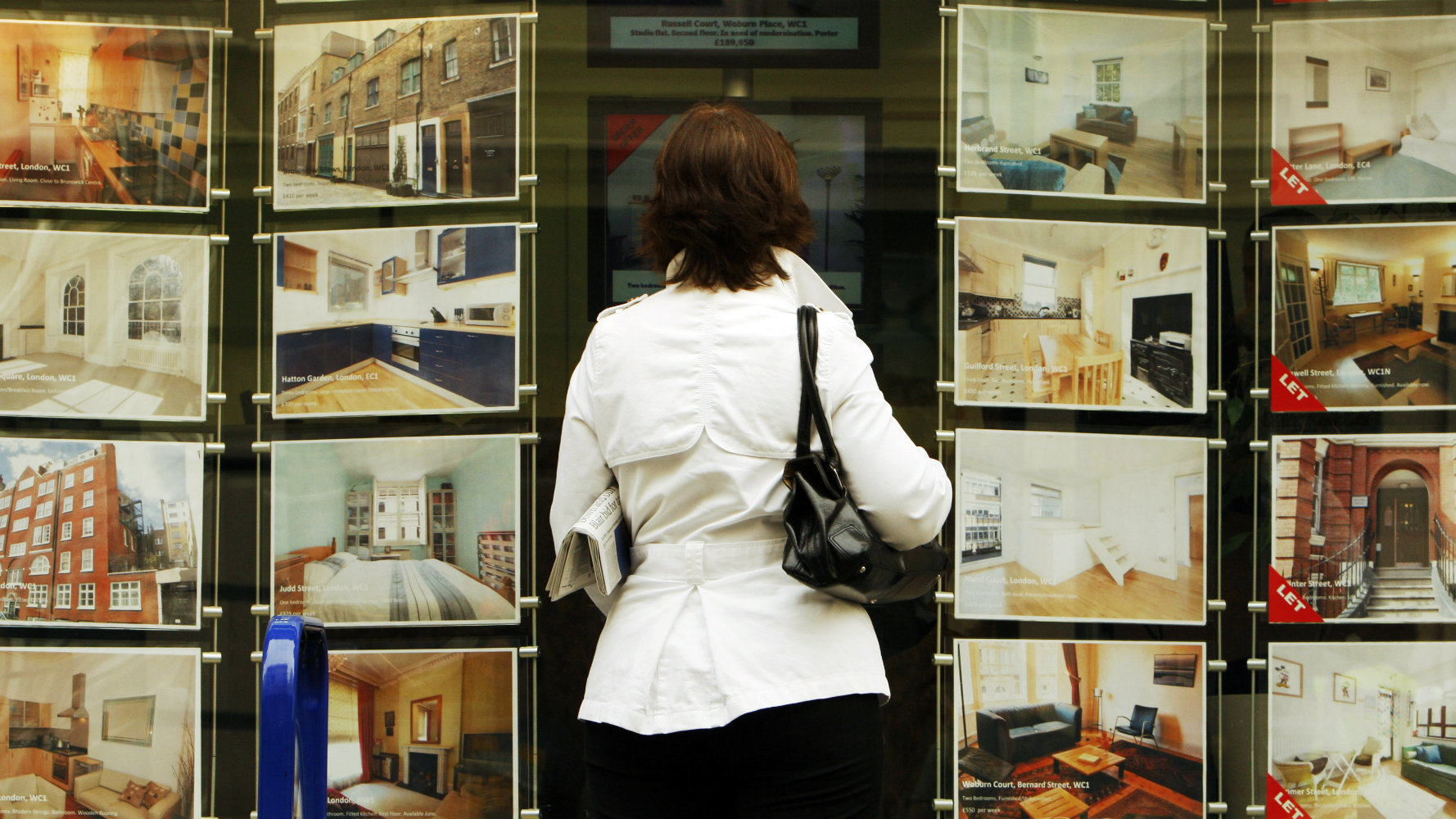 A woman looks at properties for sale in the window of an estate agent in central London.