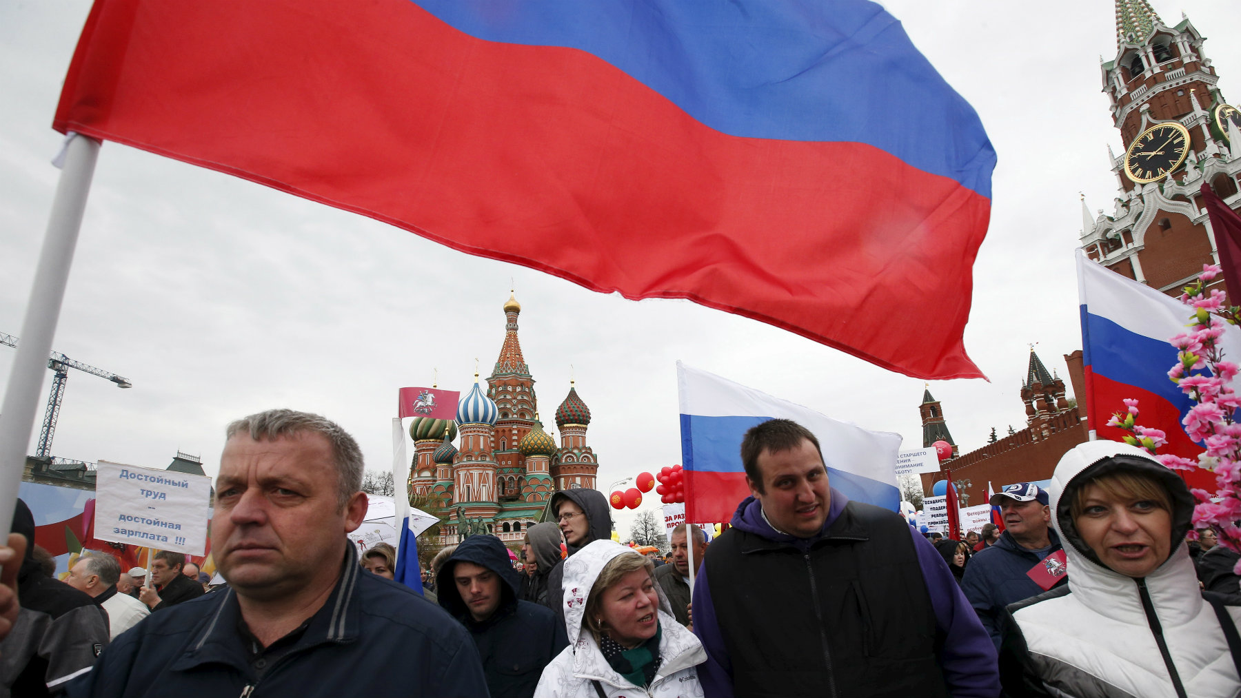 People walk with flags at Red Square during a 2015 May Day rally in Moscow.