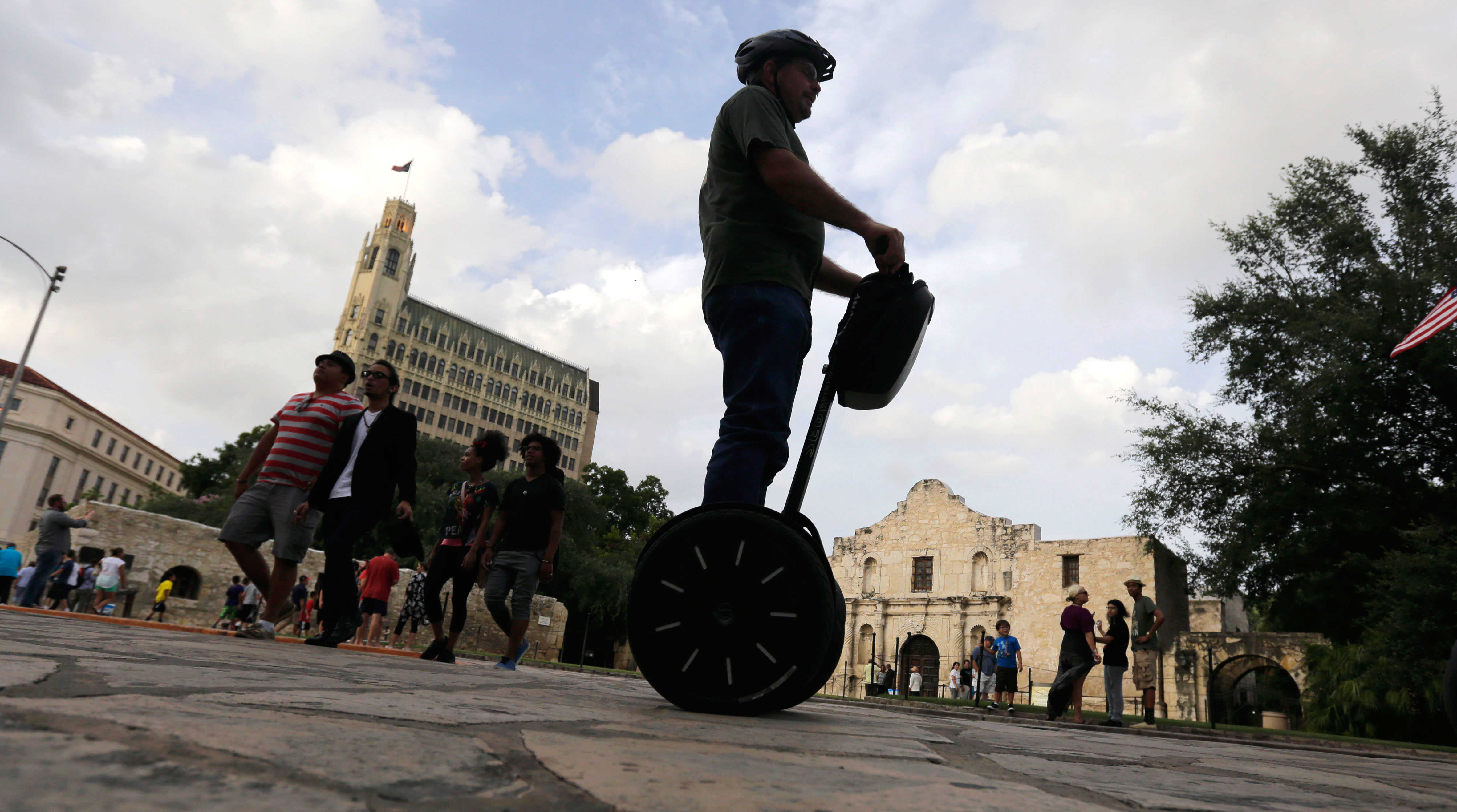 A visitor passes the Alamo on a Segway, Wednesday, July 8, 2015, in downtown San Antonio. San Antonio is one of Texas' top tourist destinations. (AP Photo/Eric Gay)