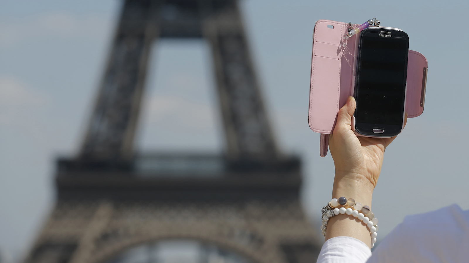 A woman uses her mobile phone to take a selfie picture at the Trocadero Square near the Eiffel Tower in Paris