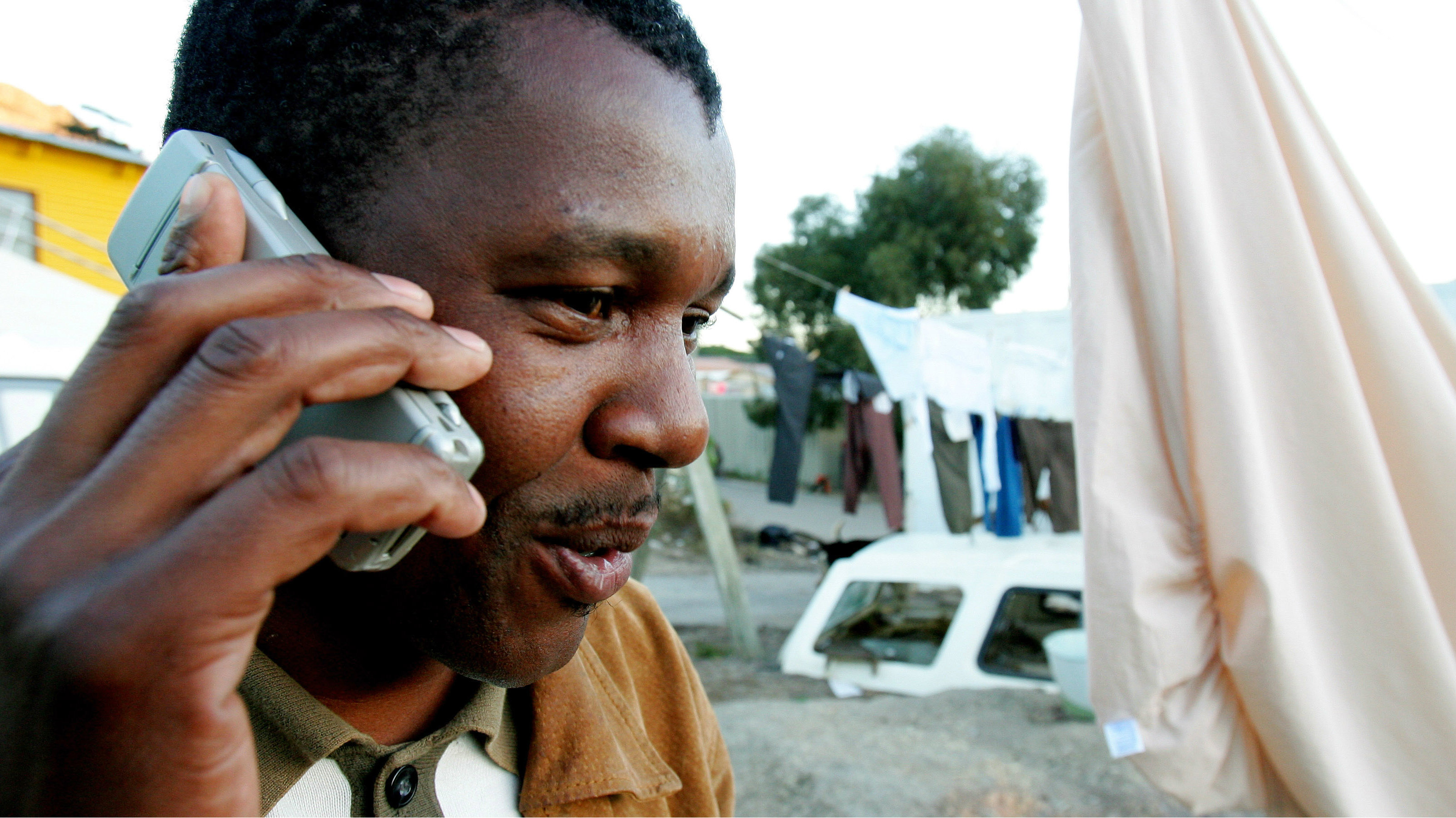 A township resident chats on his mobile phone in Hout Bay near Cape Town in this June 22, 2006 file photo. Mobile operators are scrambling to gain a foothold in Africa, where cell phone penetration hovers at just 15 percent and growth is ripe for those with a stomach for risk. But a decade after mobile technology took off on the continent, most affluent urbanites already have phones, making poor rural areas the new battleground for operators seeking growth. Picture taken June 22, 2006. To match feature TELECOMS AFRICA RURAL REUTERS/Mike Hutchings (SOUTH AFRICA)