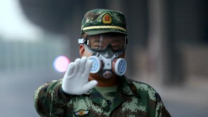 A paramilitary policeman wearing a mask gestures to the photographer to stop as he blocks a road leading to the evacuated residential area and explosion site, at Binhai new district in Tianjin, China, August 17, 2015.