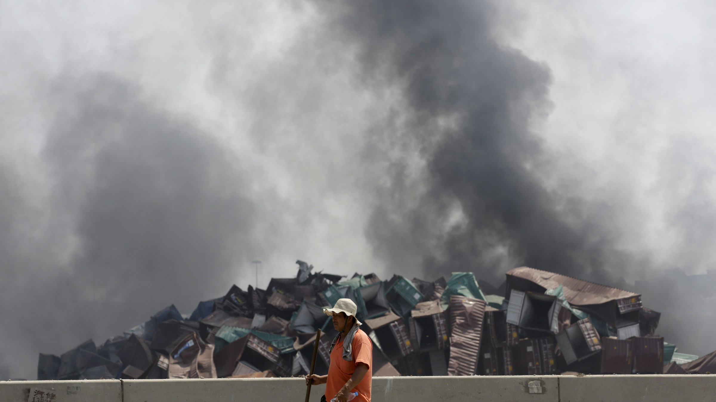 A worker walks as smokes rises near the site of the explosions at the Binhai new district, Tianjin