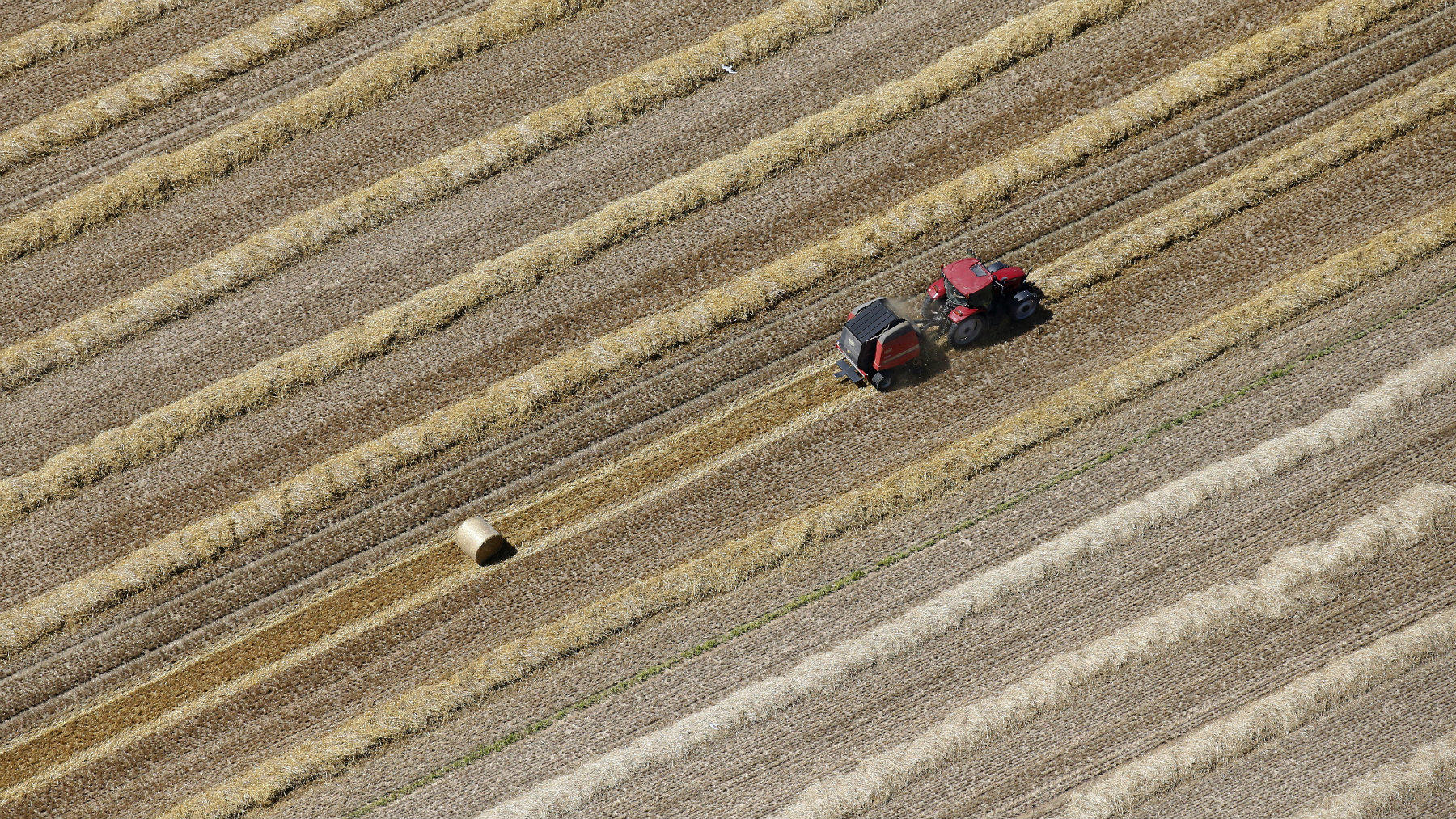 An aerial view shows a French farmer in his tractor making bales of straw after wheat harvest in his field.