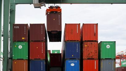 A crane lifts a cargo container at a port in Tokyo.