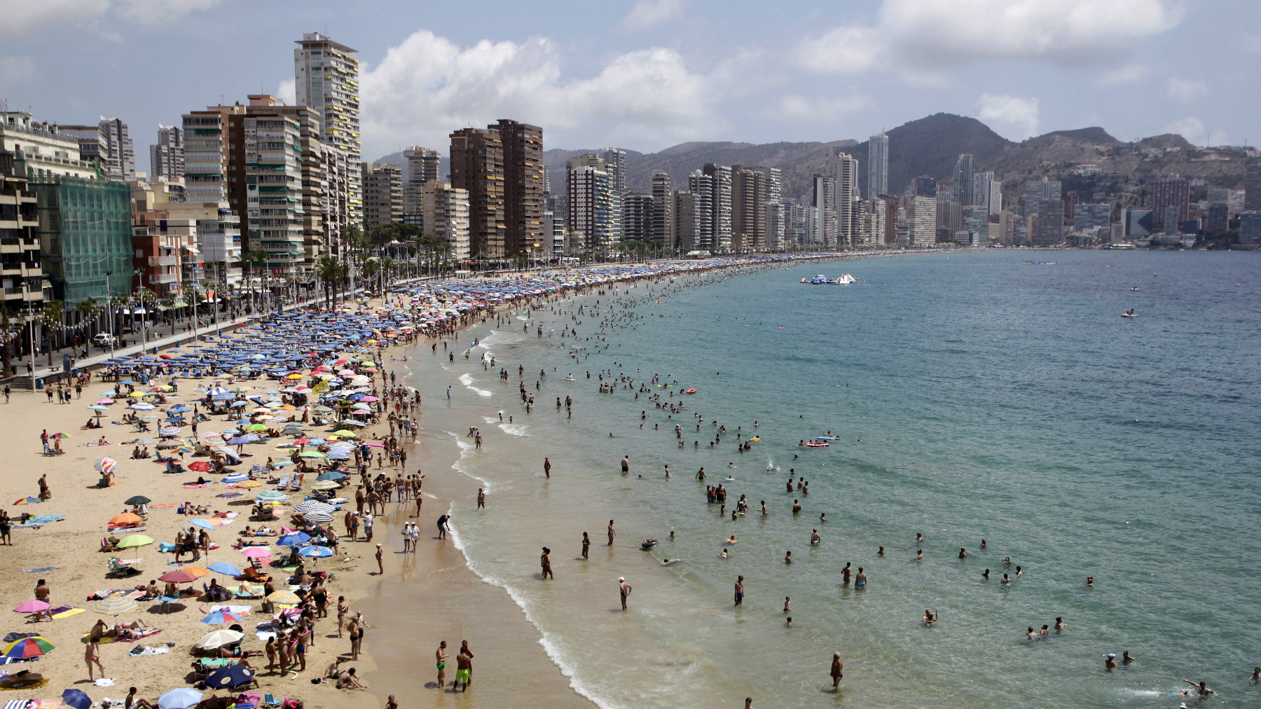 People relax at the beach during a hot summer day in Benidorm, Spain.
