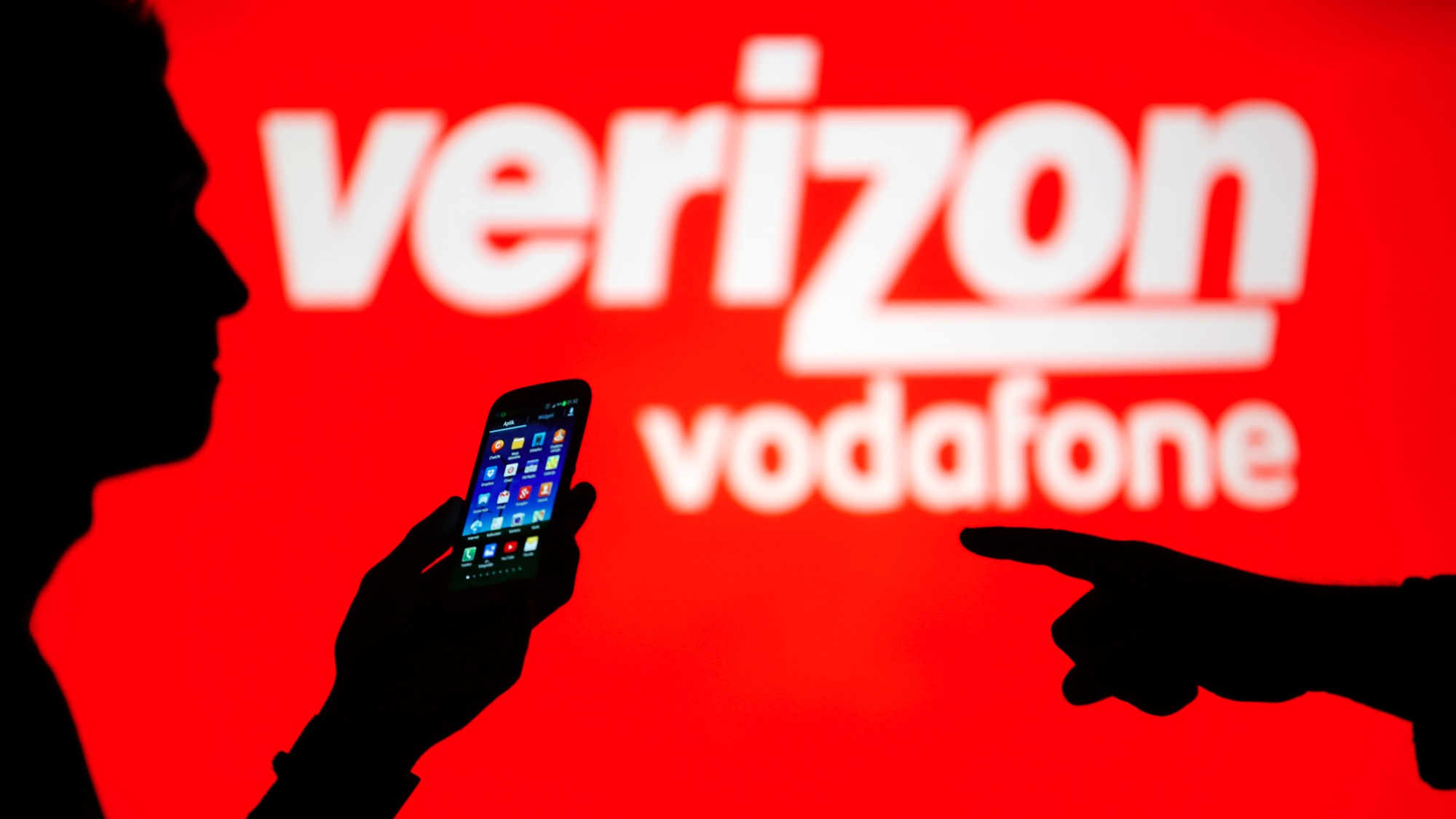 A man is silhouetted against a video screen with Vodafone and Verizon texts as he poses with a Samsung Galaxy S3 in this photo illustration taken in the central Bosnian town of Zenica, September 3, 2013. Picture taken September 3. REUTERS/Dado Ruvic (BOSNIA AND HERZEGOVINA - Tags: BUSINESS TELECOMS)