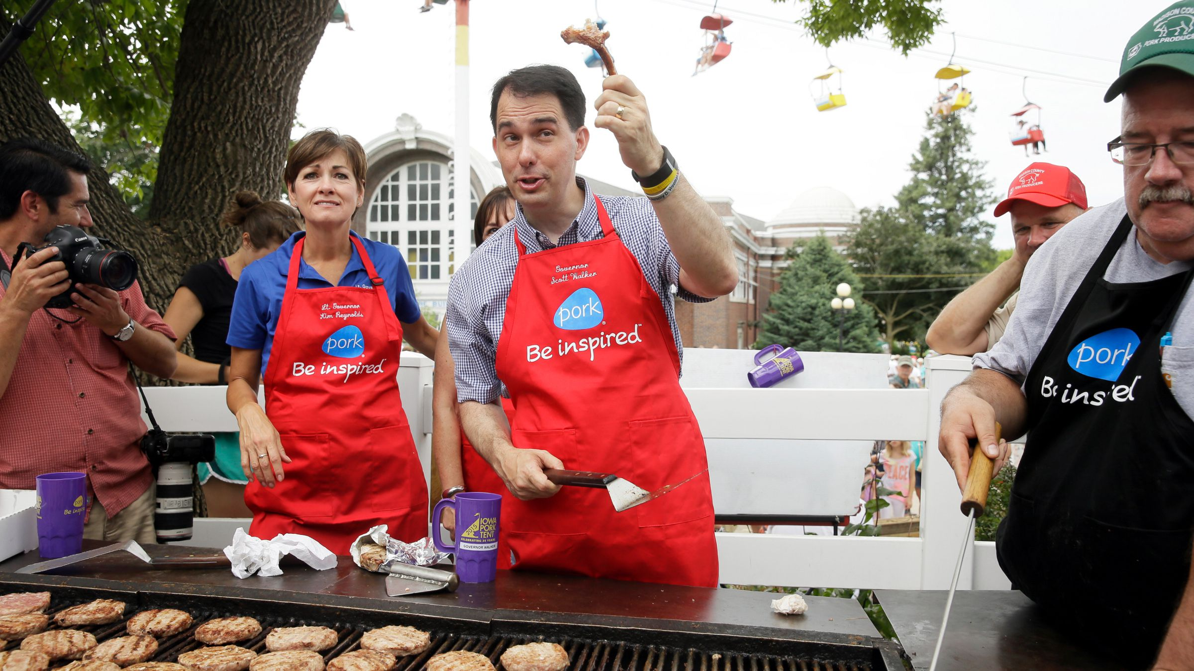 Republican presidential candidate Wisconsin Gov. Scott Walker holds up a pork chop bone while working the grill at the Iowa Pork Producers tent during a visit to the Iowa State Fair, Monday, Aug. 17, 2015, in Des Moines, Iowa.