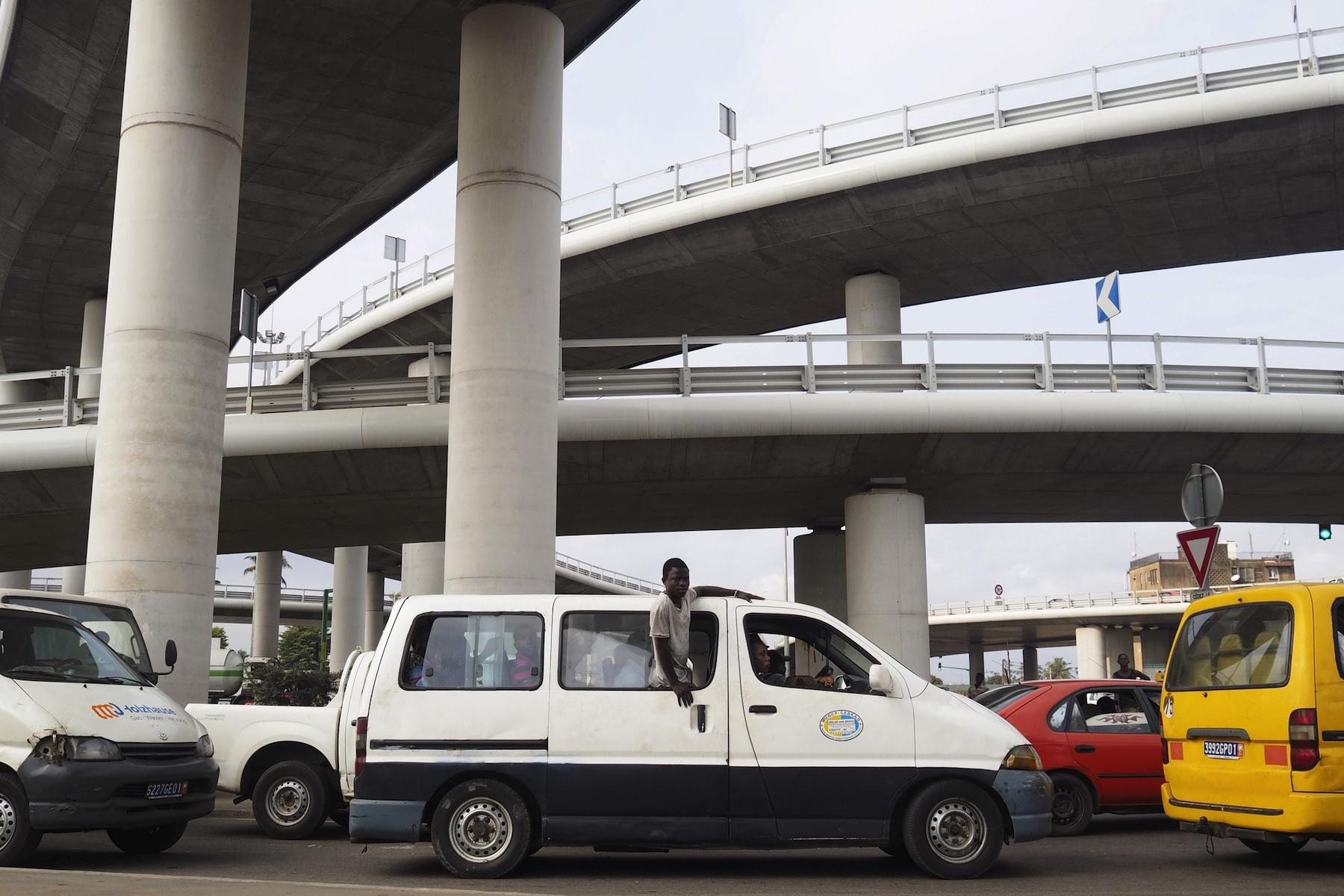 A commuter van drives underneath the newly constructed Henri Konan Bedie bridge in Abidjan.