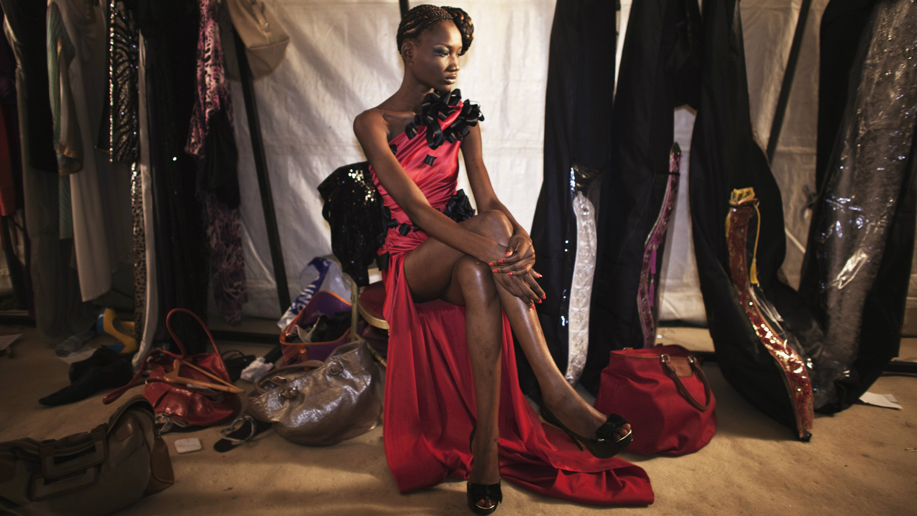 Model Nafissatou Gningue wears a creation by Egyptian designer Tito backstage during the 10th annual Dakar Fashion Week June 16, 2012.