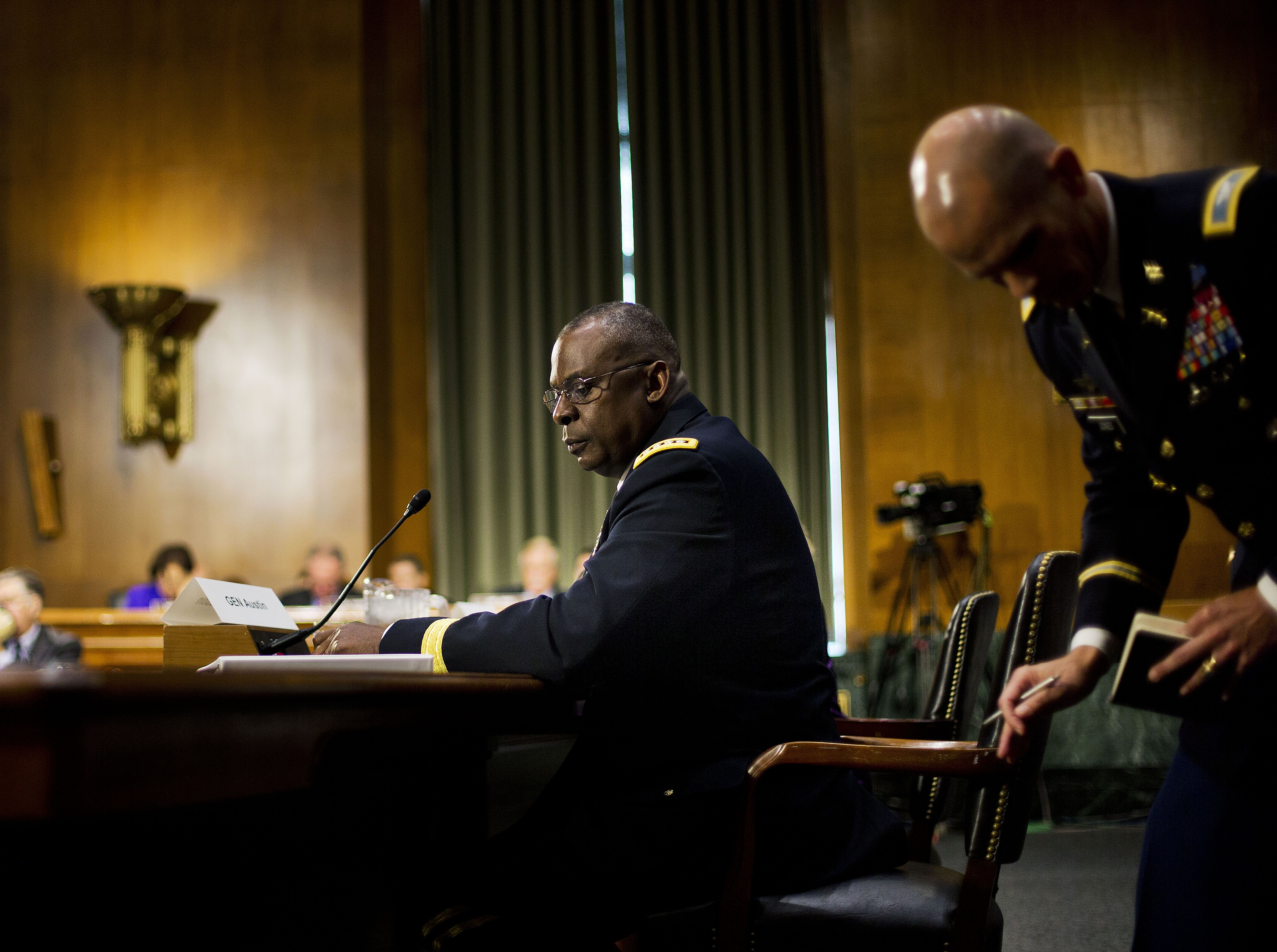 """US Central Command Commander Gen. Lloyd Austin III, center seated, looks back to his military aide while testifying on Capitol Hill in Washington, Wednesday, Sept. 16, 2015, before the Senate Armed Services Committee hearing on 'US military operations to counter the Islamic State in Iraq'. Austin vowed to take """"appropriate action"""" if an investigation indicates that senior defense officials altered intelligence reports on the Islamic State and other militant groups in Syria to exaggerate progress being made against the terrorist groups. (AP Photo/Pablo Martinez Monsivais)"""
