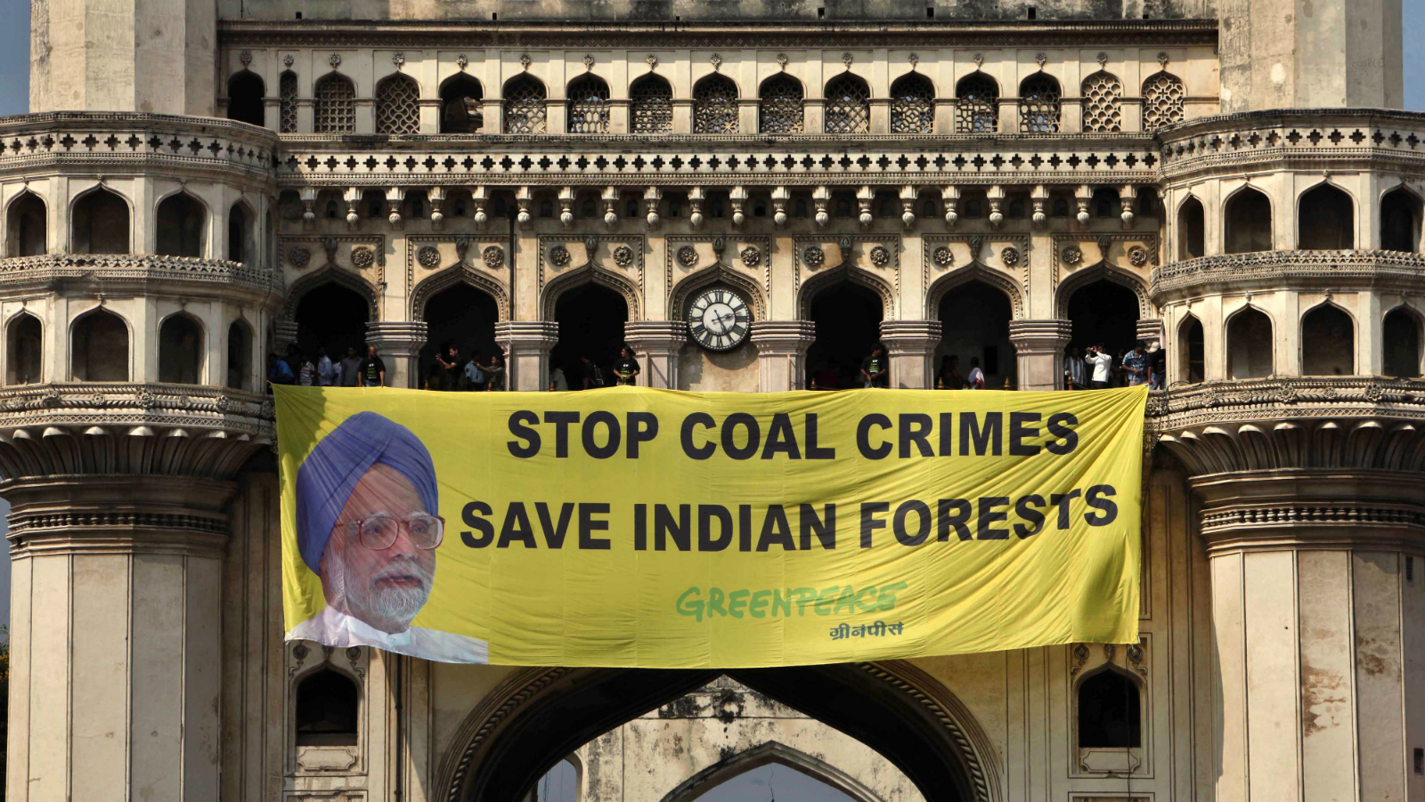 Greenpeace activists hang a banner with a photo of Indian Prime Minister Manmohan Singh atop the Charminar monument in Hyderabad, India, Monday, Oct. 8, 2012. The activists were protesting against India hosting the U.N. summit on biodiversity even as Indian forests are being destroyed due to coal mining. Singh's government was recently accused of irregular sales of coal blocks that India's auditor said cost the country's treasury tens of billions.