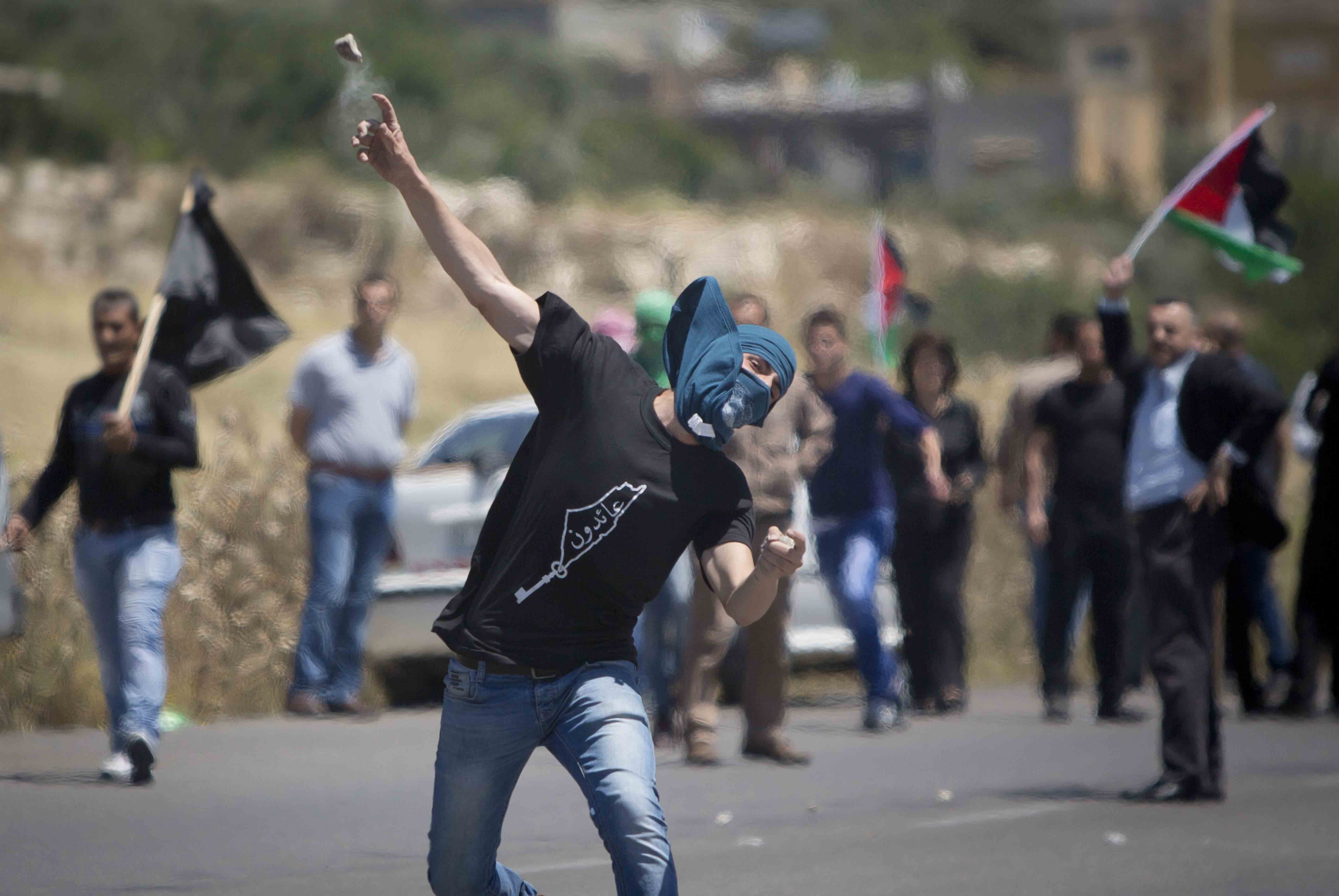 CORRECTS SECOND SENTENCE - A Palestinian throws a stone at Israeli troops during clashes after a rally marking Nakba Day at Hawara checkpoint near the West Bank city of Nablus, Saturday, May 16, 2015. Palestinians annually mark the Nakba Day, or the Day of the Catastrophe, when hundreds of thousands of Palestinians fled, or were expelled from their homes during the first Israeli-Arab war in 1948. (AP Photo/Majdi Mohammed)
