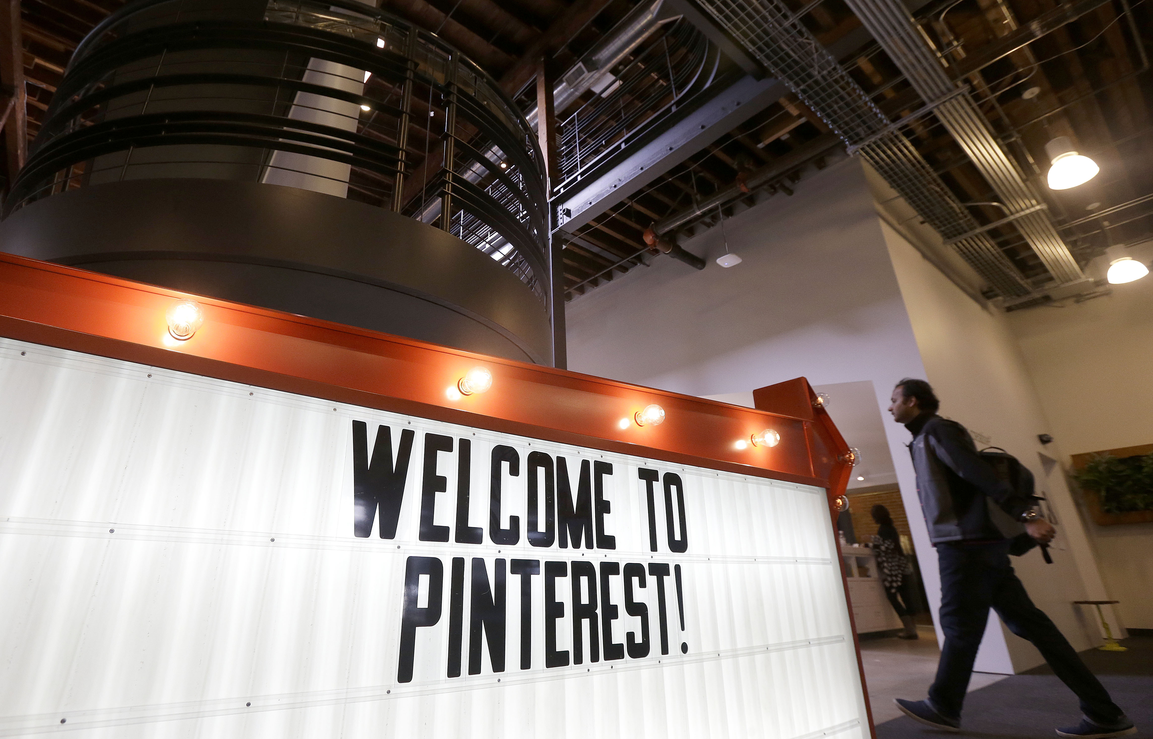 A man walks past a sign at the Pinterest office in San Francisco, Wednesday, April 1, 2015. The San Francisco-based venture capital darling celebrated its fifth birthday in March 2015. (AP Photo/Jeff Chiu)