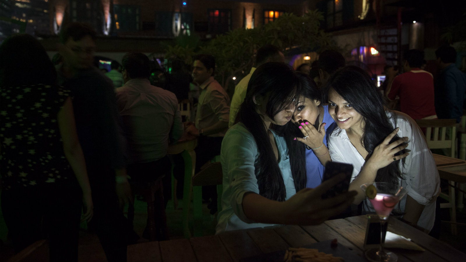 """In this June 11, 2015 photo, Indian girls take a selfie at a party hosted by """"TrulyMadly,"""" one of India's online dating apps in Gurgaon, India. Hundreds of thousands of young Indians are nervously exploring online dating apps, breaking with India's centuries-old traditions governing marriage and social conduct. The dating app market has exploded in recent years, with more than a dozen companies operating in the country and more than a million smartphone users who have downloaded at least one of them."""