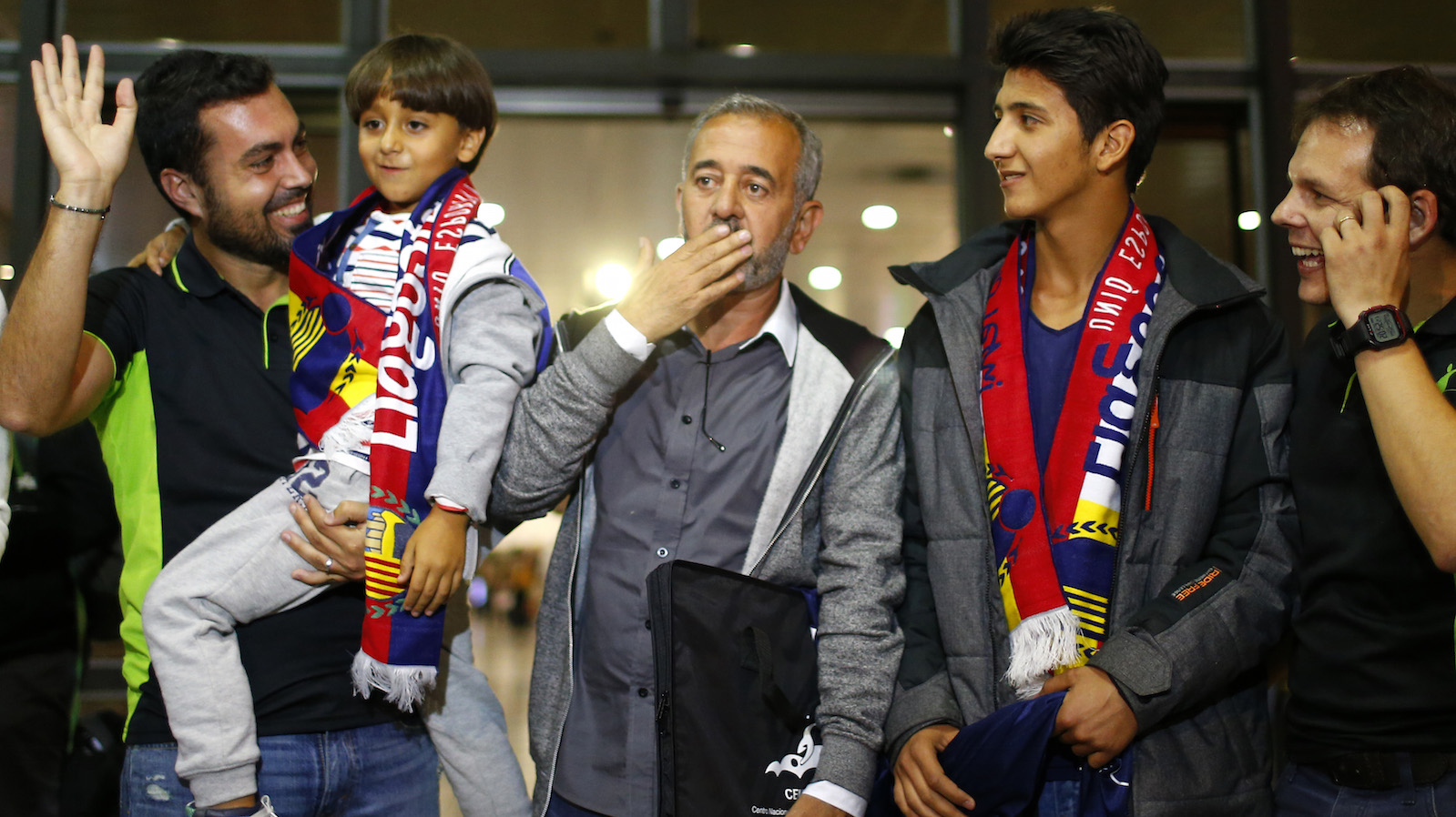 Syrian Osama Abdul Mohsen, center, reacts next to his son Zaid, left, as they arrive at the Barcelona train station on Wednesday, Sept.16, 2015. The Syrian refugee tripped at a border hotspot by a Hungarian journalist in an incident captured on video that generated global outrage will live in a Madrid suburb after a Spanish soccer academy convinced him to take an apartment offer and help to rebuild his life, an official with the school said Wednesday. Osama Abdul Mohsen was on a train expected to arrive in Madrid at midnight Wednesday.