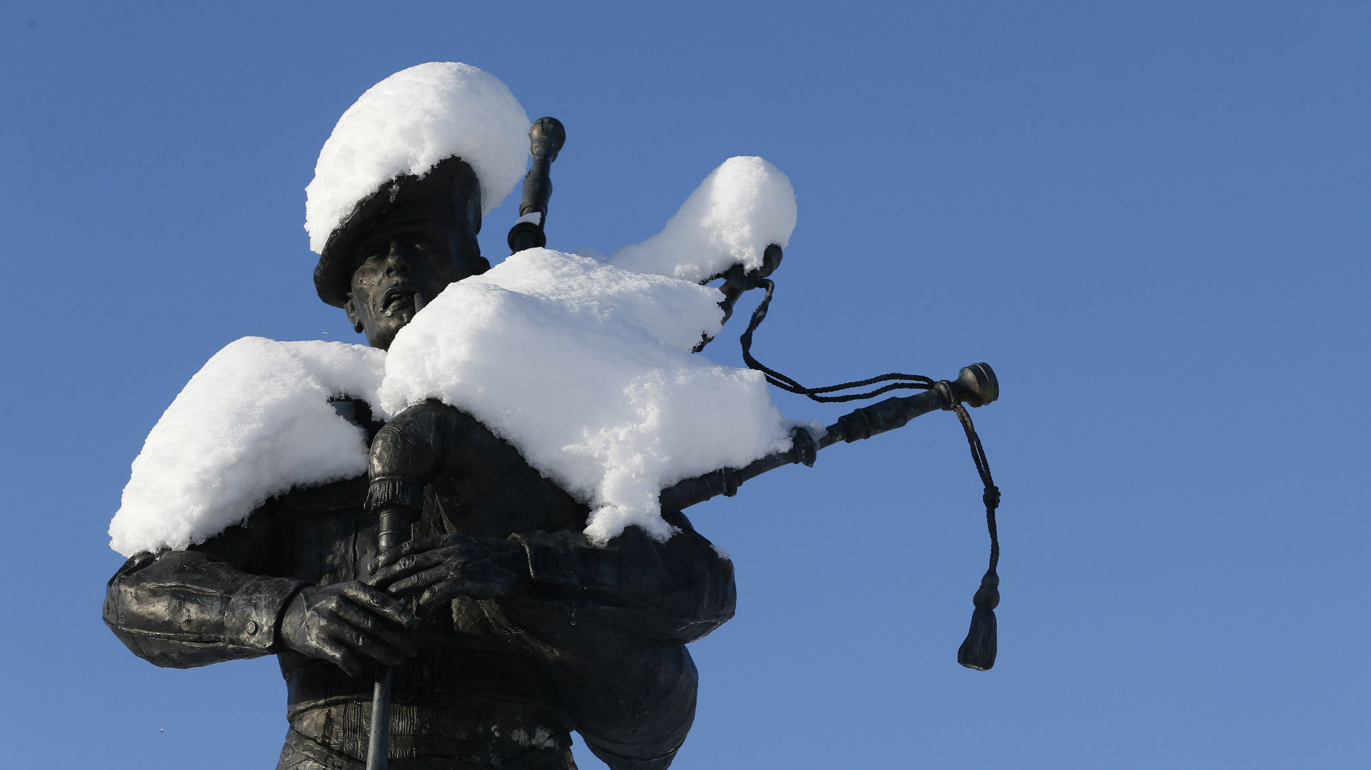 A statue of a piper is covered in snow in Bruar.