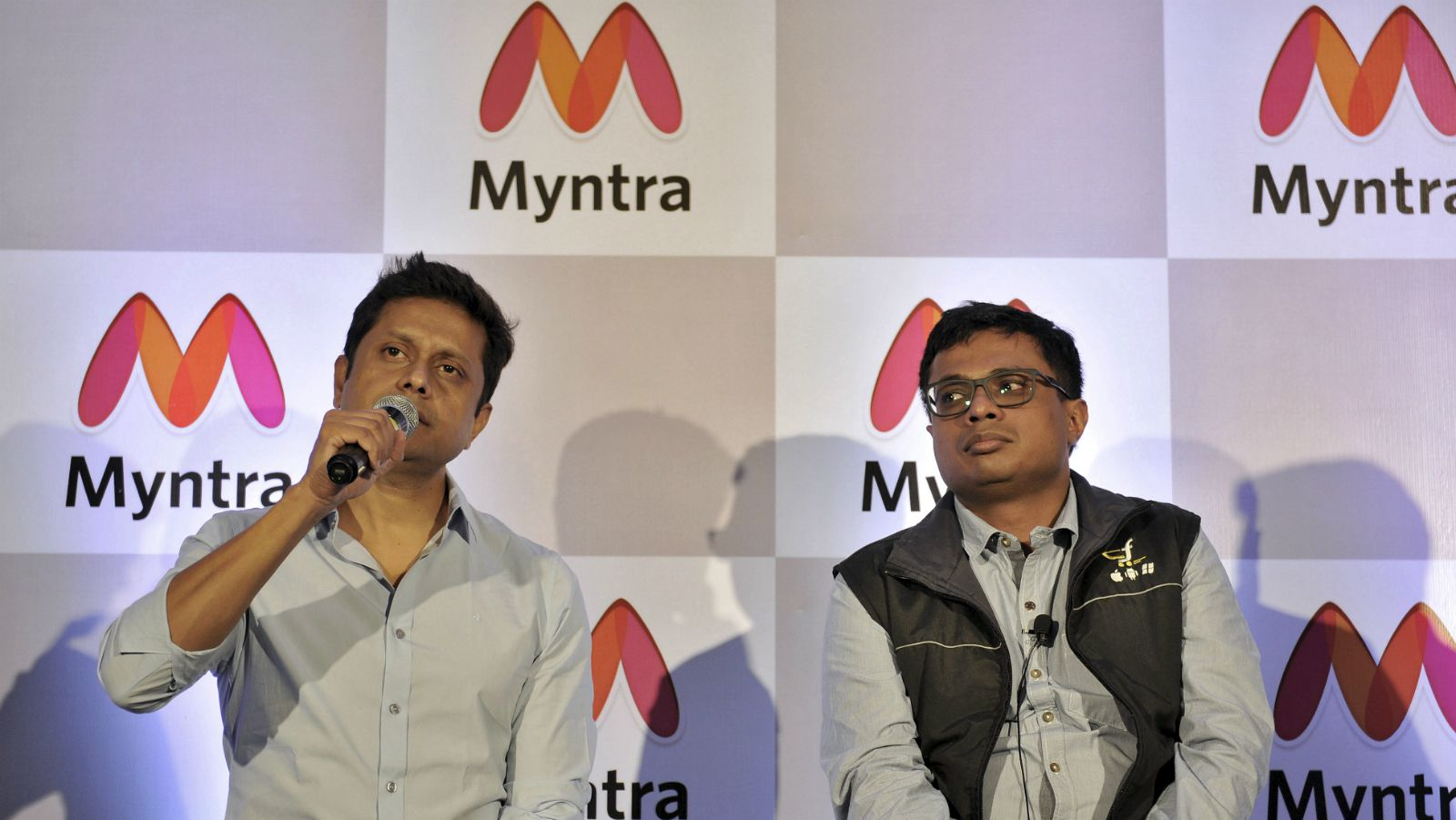 Chief Executive Officer of online fashion retailer Myntra, Mukesh Bansal (L) speaks during a news conference as Sachin Bansal, co-founder of India's biggest e-commerce firm Flipkart, watches in Bengaluru, India, May 12, 2015.