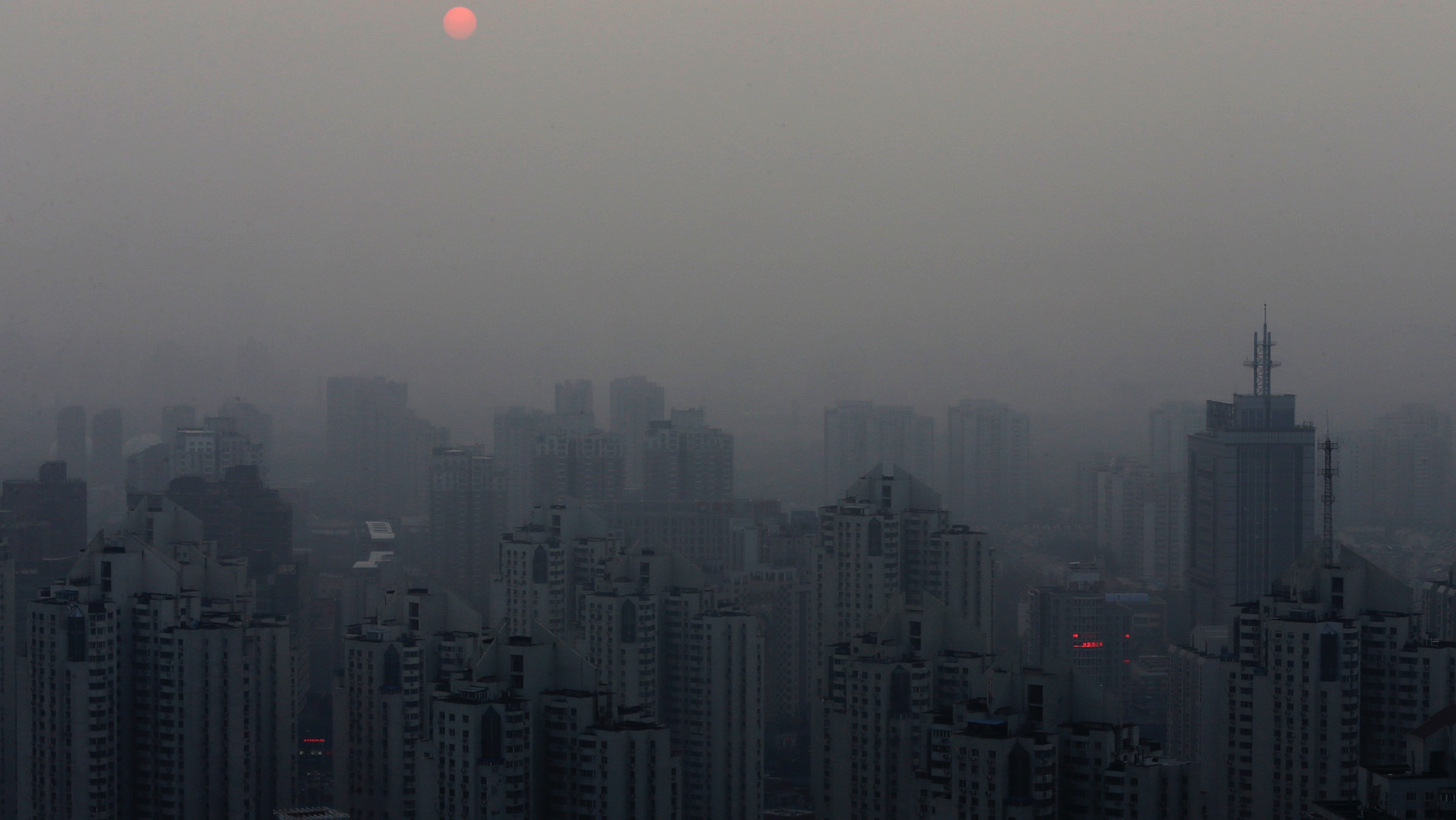 The sun sets above residential buildings on a hazy day in Beijing