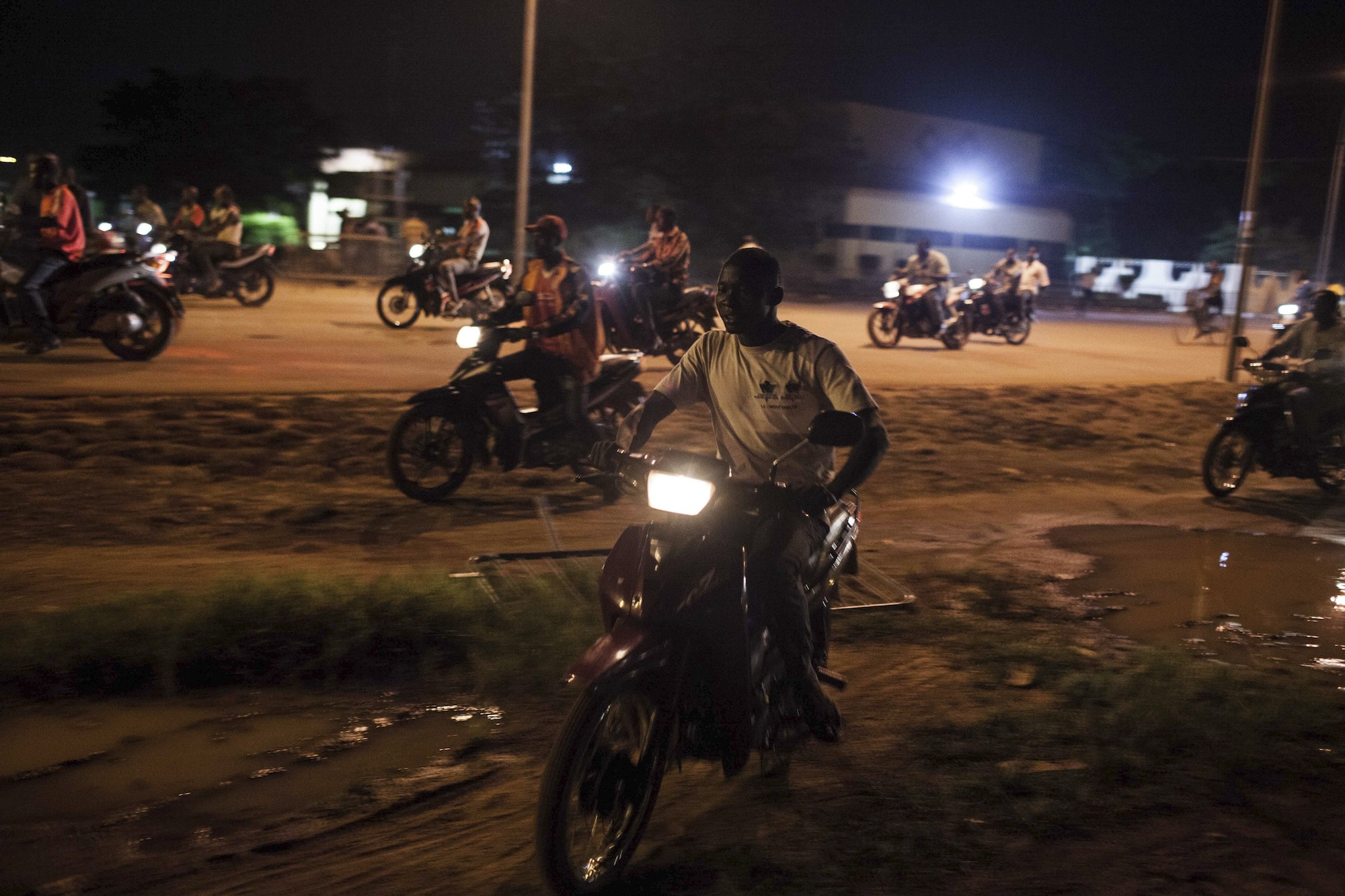 People on motor bikes used as taxi's drive around after demonstrations near the presidential palace as soldiers arrested Burkina Faso's transitional president and prime minister in Ouagadougou.
