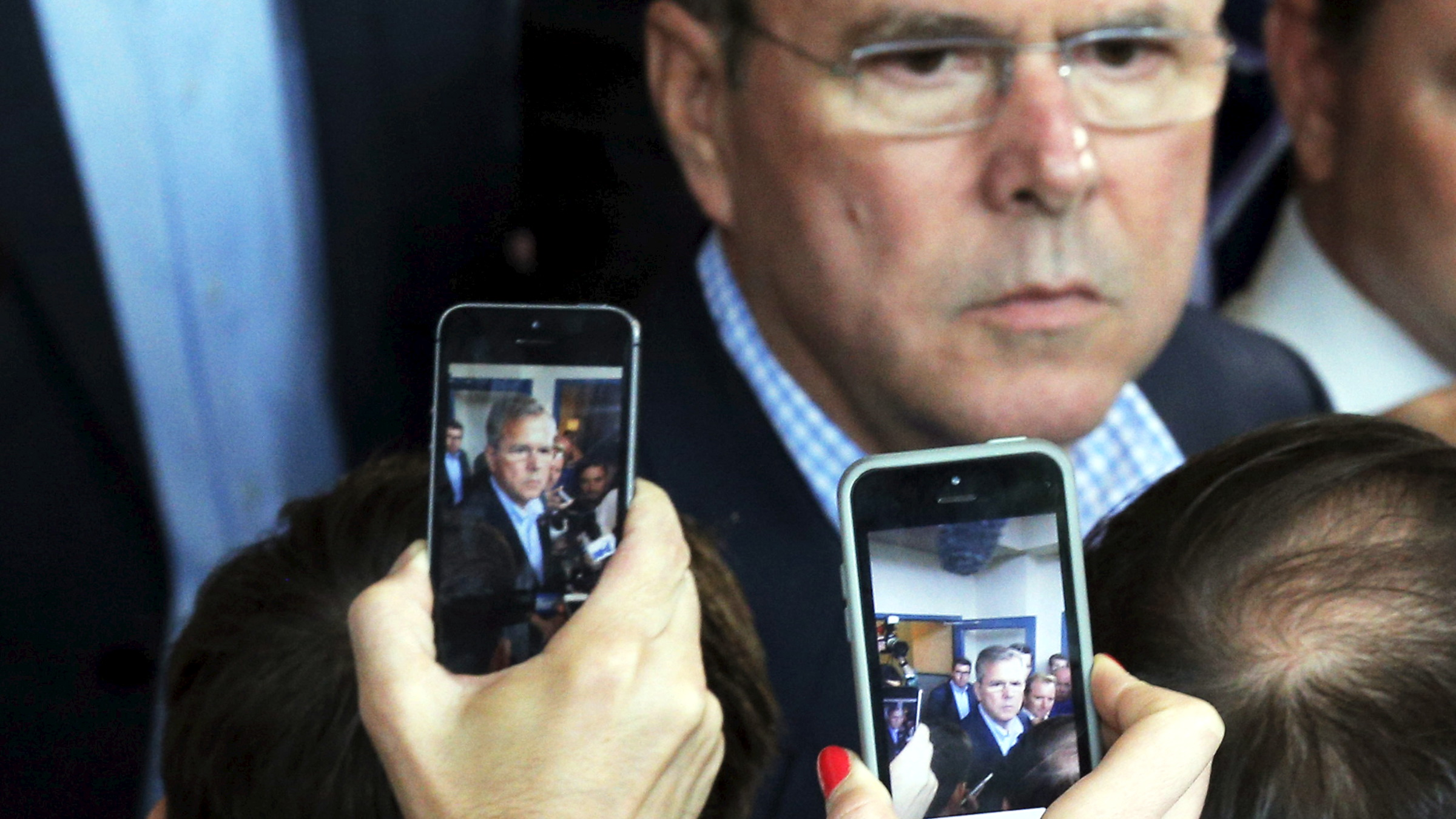 Reporters use their mobile phones to record potential 2016 Republican presidential candidate and former Florida Governor Jeb Bush as he answers questions after speaking at a business roundtable in Portsmouth, New Hampshire May 20, 2015.