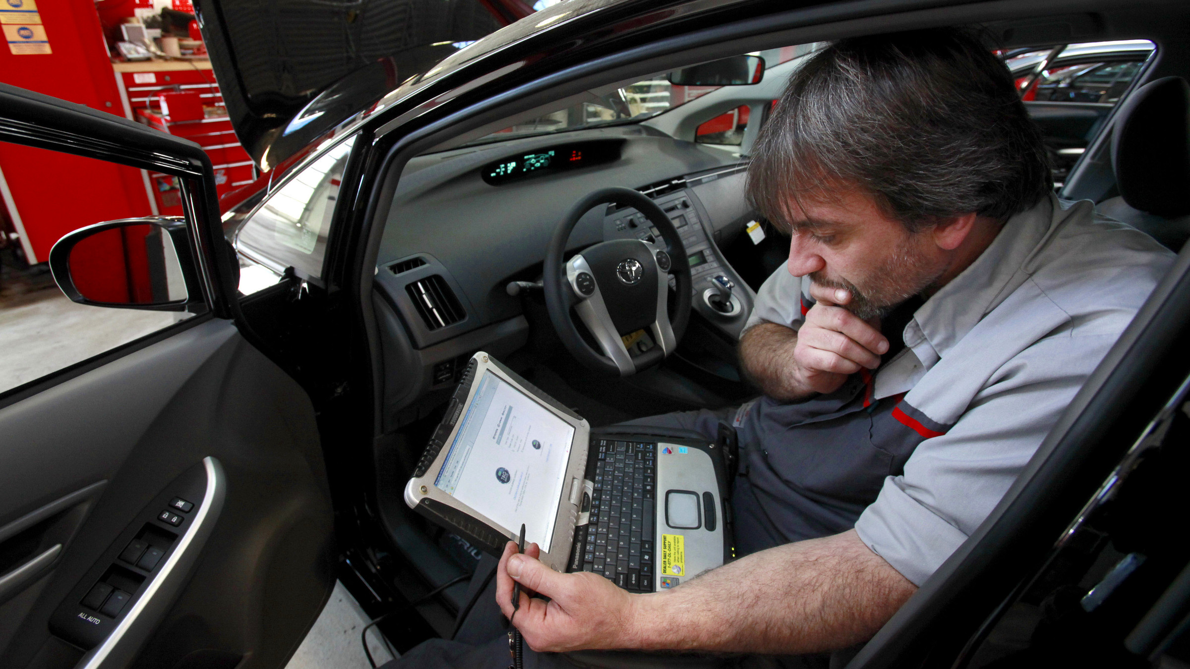FILE - In this Feb. 9, 2010 file photo, master diagnostic technician Kurt Juergens, of Foxborough, Mass., uses a laptop computer to diagnose and repair the brake system on a 2010 Toyota Prius in the repair shop of a Toyota dealership, in Norwood, Mass. A pair of hackers maneuvered their way into the computer systems of a 2010 Toyota Prius and 2010 Ford Escape through a port used by mechanics. The hackers showed that they could slam on the brakes at freeway speeds, jerk the steering wheel or even shut down the engine, all from their laptop computers. The work demonstrates vulnerabilities with the growing number of car computers, about 20 on older models and up to 70 on sophisticated luxury cars.