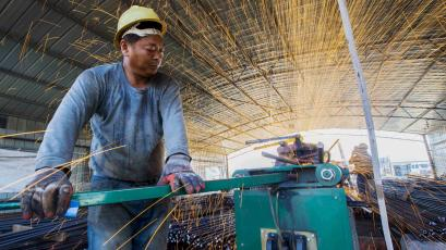 A worker cuts steel bars at a railway bridge construction site in Lianyungang, Jiangsu province.