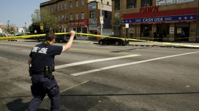 A police crime scene technician heads in to document evidence at the scene of a shooting at the intersection of West North Avenue and Druid Hill Avenue in West Baltimore, Maryland May 30, 2015.