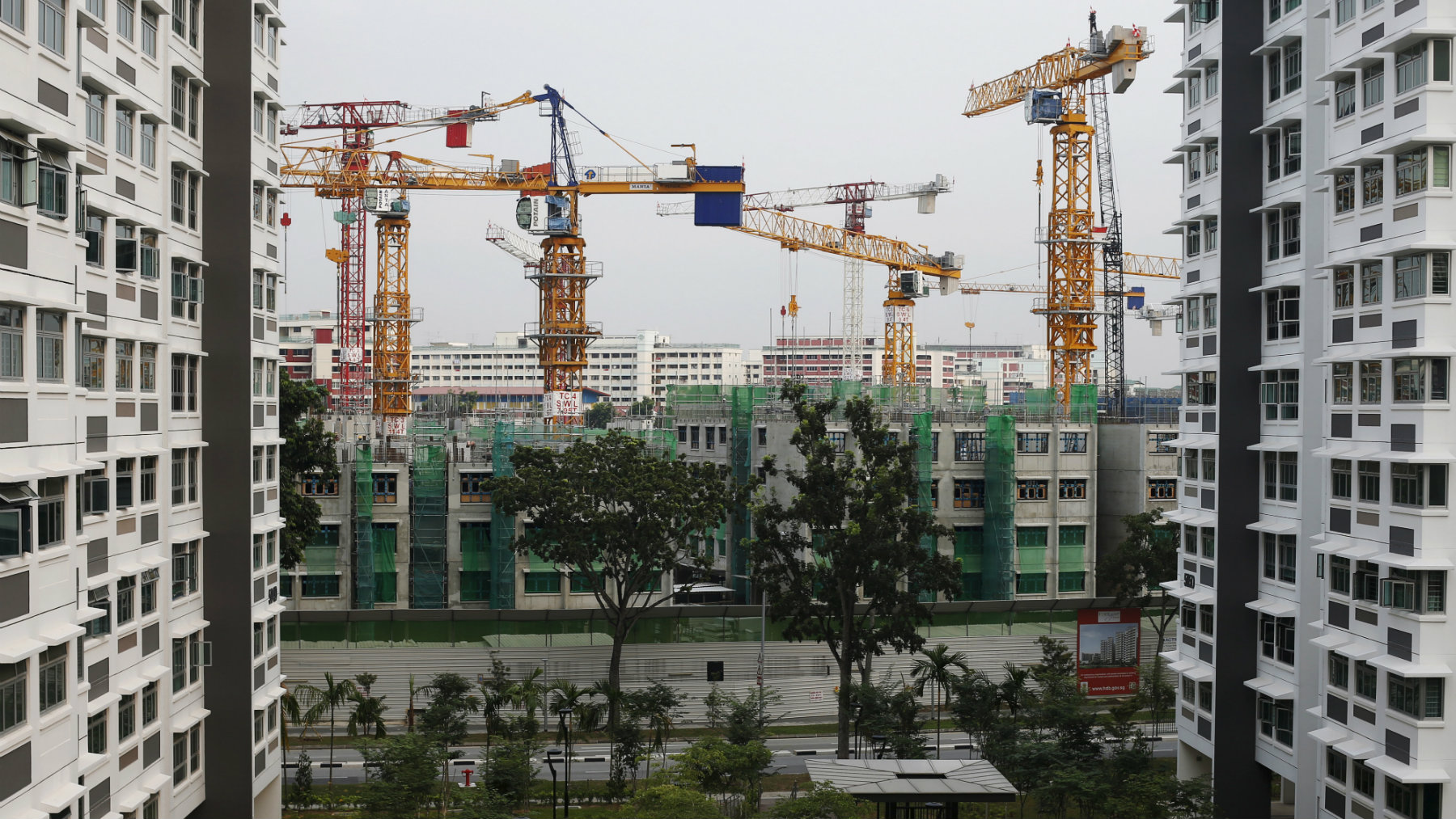 A view of a construction site of a public residential apartment estate next to completed estates in Singapore September 7, 2015. Singapore's private home prices are expected to extend their longest stretch of decline in over a decade as an imminent U.S. interest rate hike threatens to push up borrowing costs, in a market where measures to cool prices have also strangled demand. Prices have fallen about 7 percent over the past seven quarters, after the government raised stamp duties and tightened lending criteria. But the pace of decline pales in comparison to the 60 percent surge of the four years to 2013, as overseas investors in particular took advantage of low interest rates. Housing prices are a hot topic in the land-starved country, home to some of the world's most expensive real estate. Prices topped the agenda in a 2011 election decided by the slimmest-ever margin, and voters at some party rallies said prices will be on their minds when they go to the polls again on Friday. Picture taken September 7, 2015. REUTERS/Edgar Su