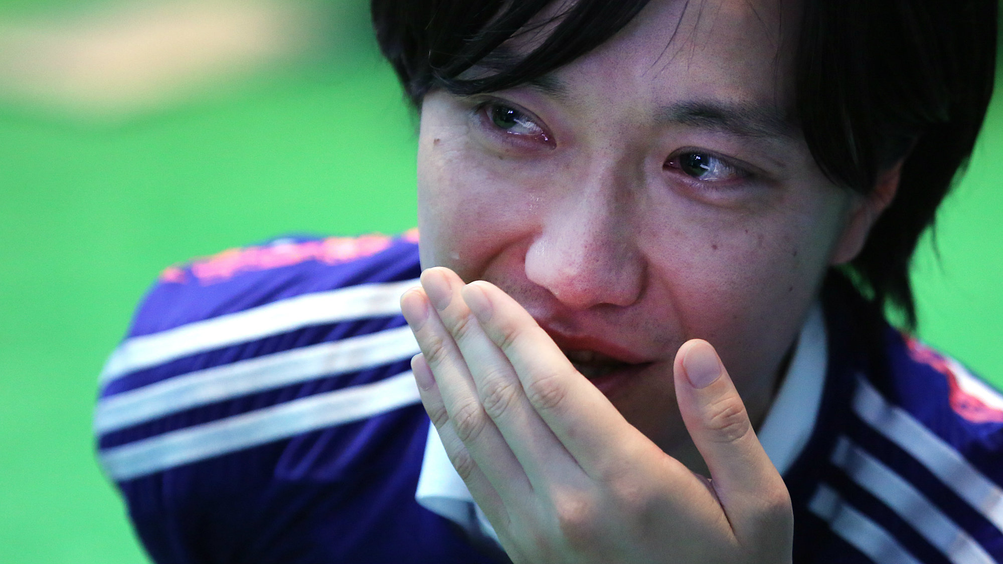A Japanese soccer fan cries after watching a live broadcasting of the World Cup soccer match between Japan and Colombia at a public viewing venue in Tokyo, Wednesday, June 25, 2014.