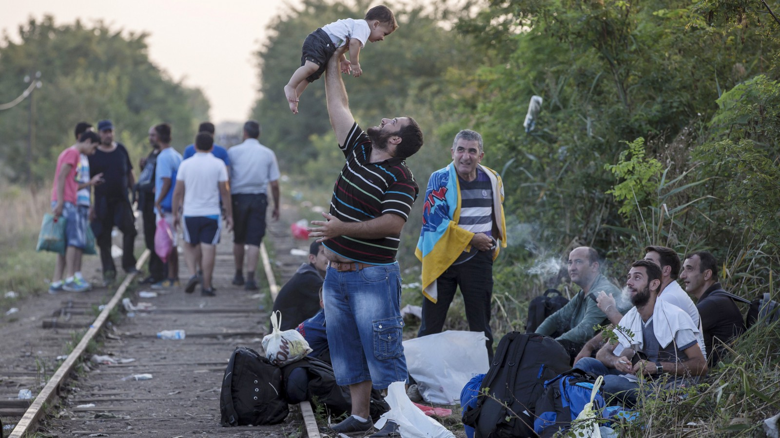 """A migrant, hoping to cross into Hungary, plays with a child along a railway track outside the village of Horgos in Serbia, towards the border it shares with Hungary, August 31, 2015. The European Union could soon fund and set up new reception facilities for asylum-seekers in Hungary as it is already doing in Italy and Greece, its migration commissioner said on Monday. Saying he would travel to Budapest soon, Dimitris Avramopoulos told reporters that the EU executive was ready to offer further help to the government as it takes in large numbers of people crossing the Balkans to reach the European Union and would """"if necessary, set up a hotspot in Hungary"""". REUTERS/Marko Djurica  TPX IMAGES OF THE DAY      - RTX1QHD8"""