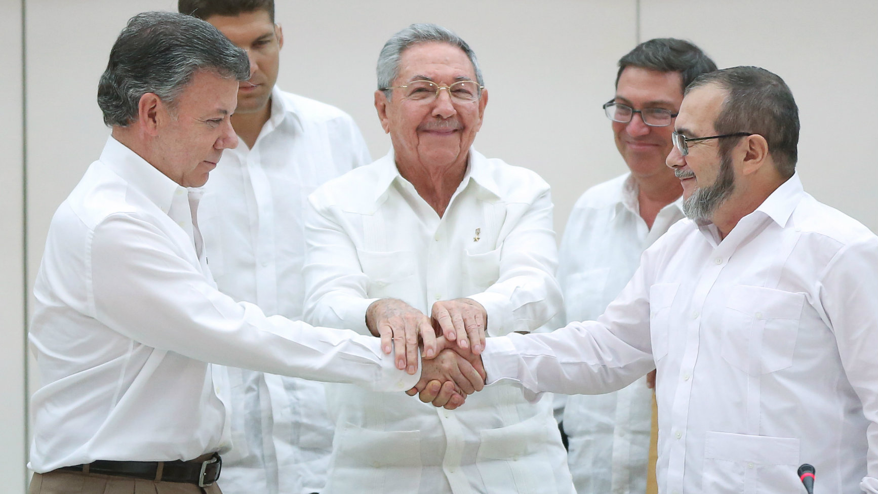 Cuba's President Raul Castro (C) stands as Colombia's President Juan Manuel Santos (L) and FARC rebel leader Rodrigo Londono, better known by the nom de guerre Timochenko, shake hands at peace talks in Havana, September 23, 2015.