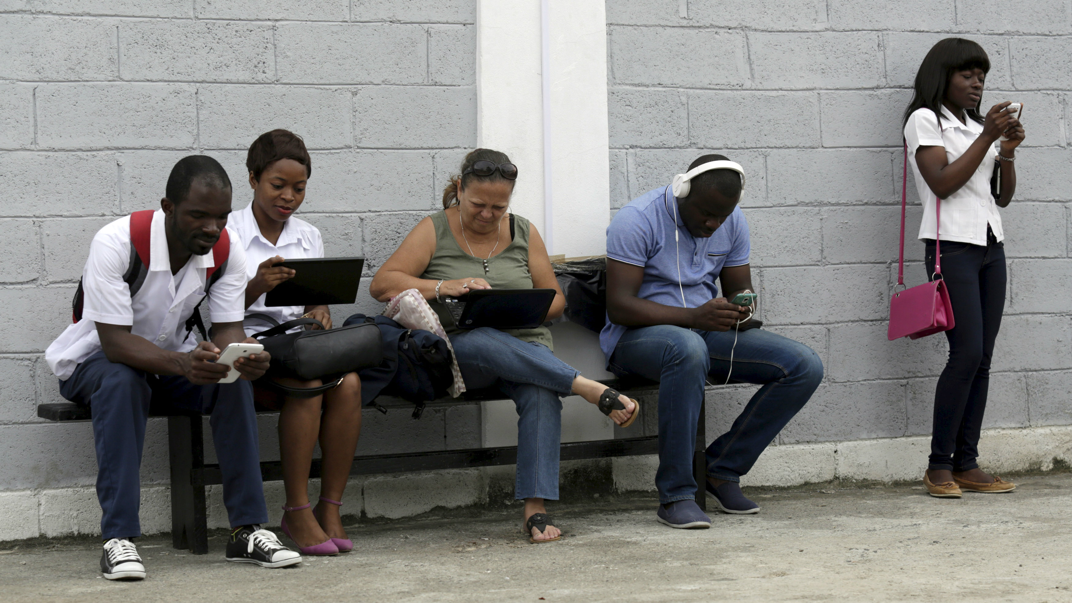 "Young people use the internet via the free wifi at the studio of Cuban artist Alexis Leyva ""Kcho"" in Havana March 24, 2015. The studio is where former Cuban president Fidel Castro has his last public appearance and the password of the wifi connection is ""Nobody surrenders here"". REUTERS/Enrique de la Osa?"