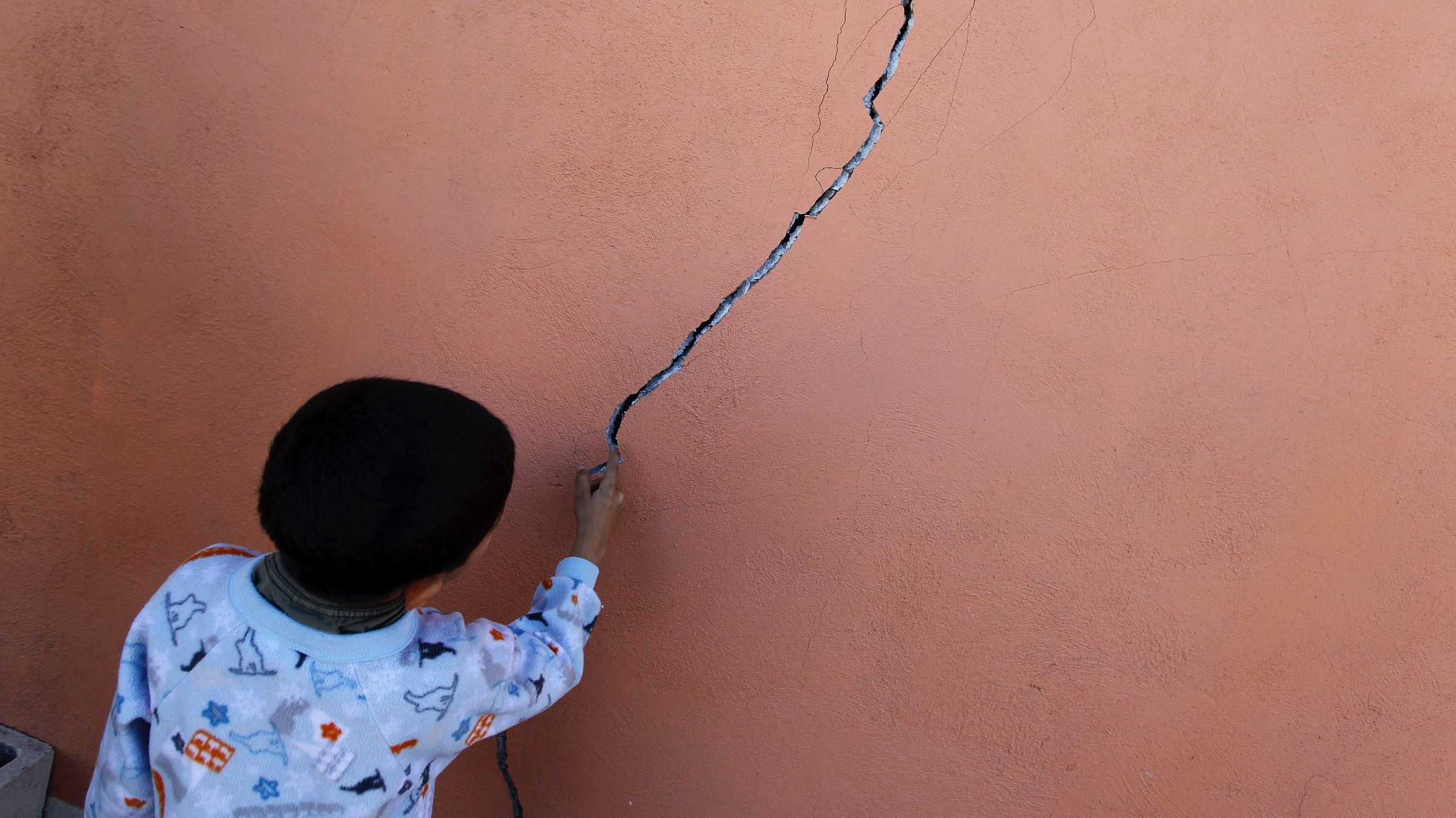 A kid touches a crack on a wall at his damaged home in the community of Oaxaca, on the outskirts of Mexicali