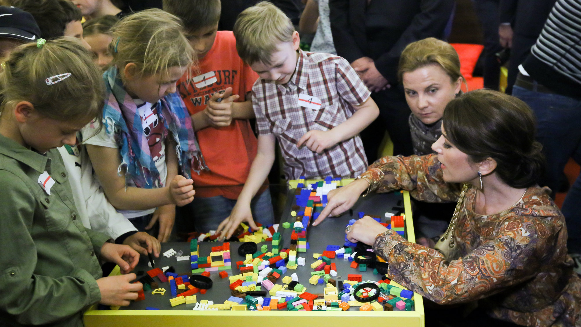 Princess Mary of Denmark (R) plays with children during the LEGO's creative workshops for children in Warsaw, Poland.