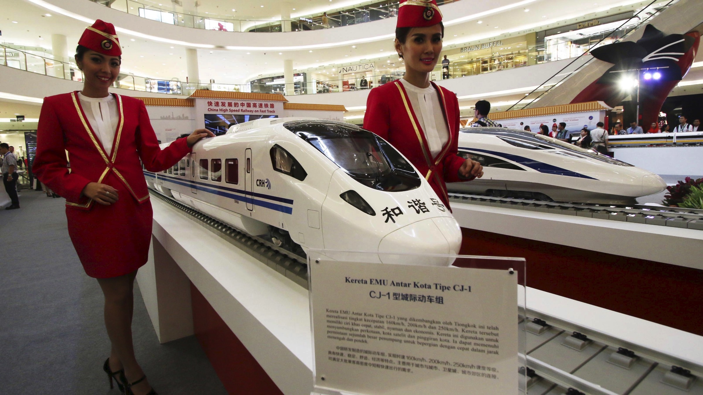 Attendants pose for a photo beside the models of a high speed train during the China High Speed Railway on Fast Track exhibition in Jakarta