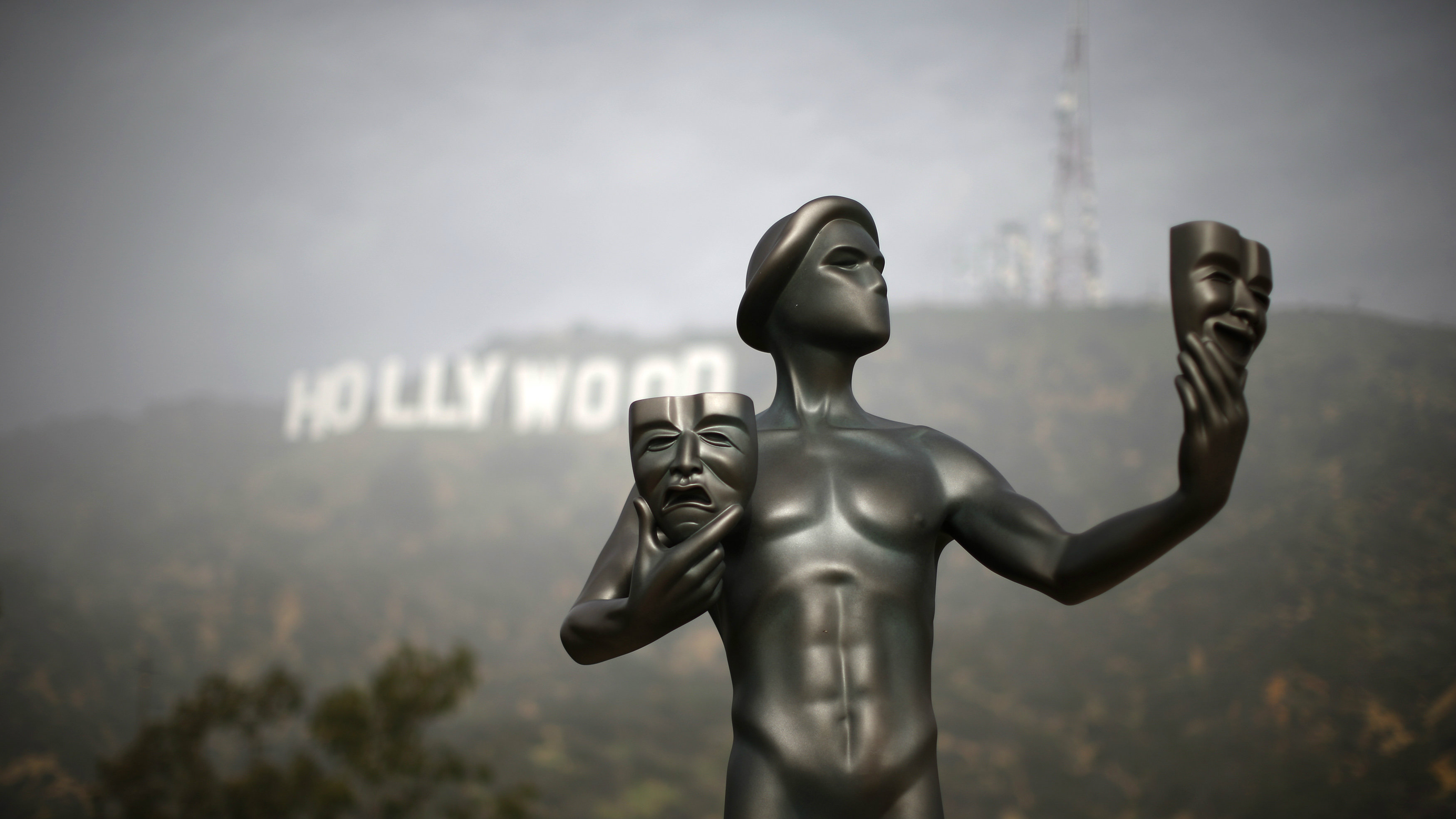A Screen Actors Guild statue is seen in front of the Hollywood sign in Los Angeles, California January 20, 2015.