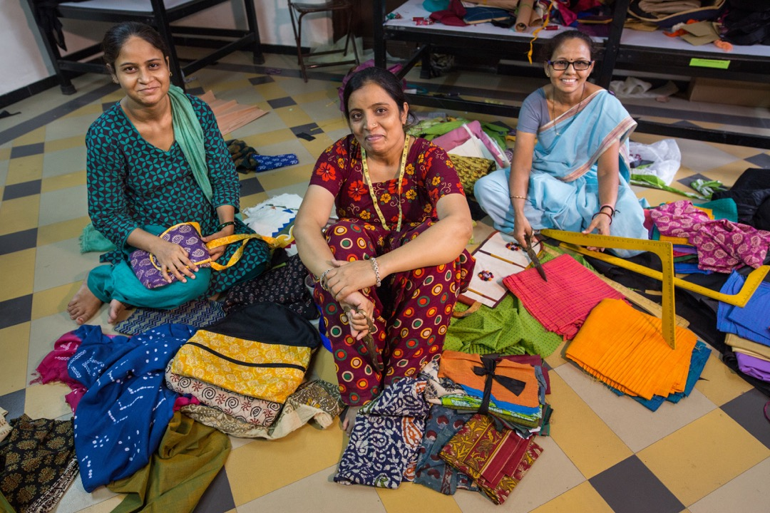 Ahmedabad, India: Rehat Rangrez (L), Noorjahan Makrani (C), and Sangeeta Parmar (R) create handcrafted bags at the Self-Employed Women's Assocation (SEWA) Artisan House. The house was opened in 2014 to support women artisans in the informal sector to continue their craft and increase their earning power. The Artisan House also sells their products, eliminating the issue of a middleman cutting into the women's small incomes.