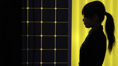 A woman is silhouetted next to a solar panel.