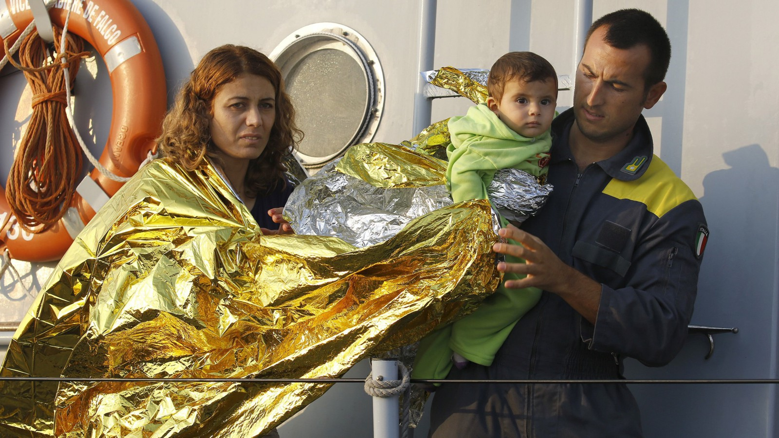 """An Italian coast guard officer helps Syrian refugees from Kobani in the port of Kos following a rescue mission off the Greek island of Kos August 10, 2015. An Italian Coast Guard vessel rescued 60 Syrian refugees drifting on a dinghy between Greece and Turkey.United Nations refugee agency (UNHCR) called on Greece to take control of the """"total chaos"""" on Mediterranean islands, where thousands of migrants have landed. About 124,000 have arrived this year by sea, many via Turkey, according to Vincent Cochetel, UNHCR director for Europe.  REUTERS/Yannis Behrakis - RTX1NQR8"""