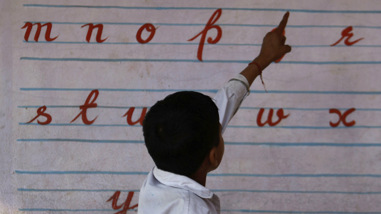 An Indian HIV positive child reads out the English alphabets at a school on the eve of World AIDS Day in Akhnoor, 50 kilometers (30 miles) from Jammu, India, Tuesday, Nov. 30, 2010. (AP Photo/Channi Anand)