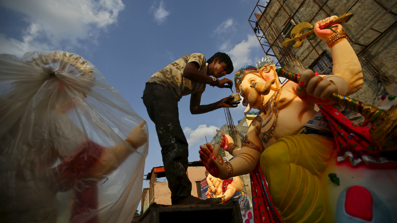 An artisan works on an idol of Hindu elephant god Ganesh, the deity of prosperity, at a roadside workshop in New Delhi, India, August 31, 2015. Work on Ganesh idols usually begins two to three months before Ganesh Chaturthi, a popular religious festival in India that will be held in September this year. During the festival the idols will be taken through the streets in a procession accompanied by dancing and singing, and to be immersed in a river or the sea in accordance with the Hindu faith. REUTERS/Anindito Mukherjee
