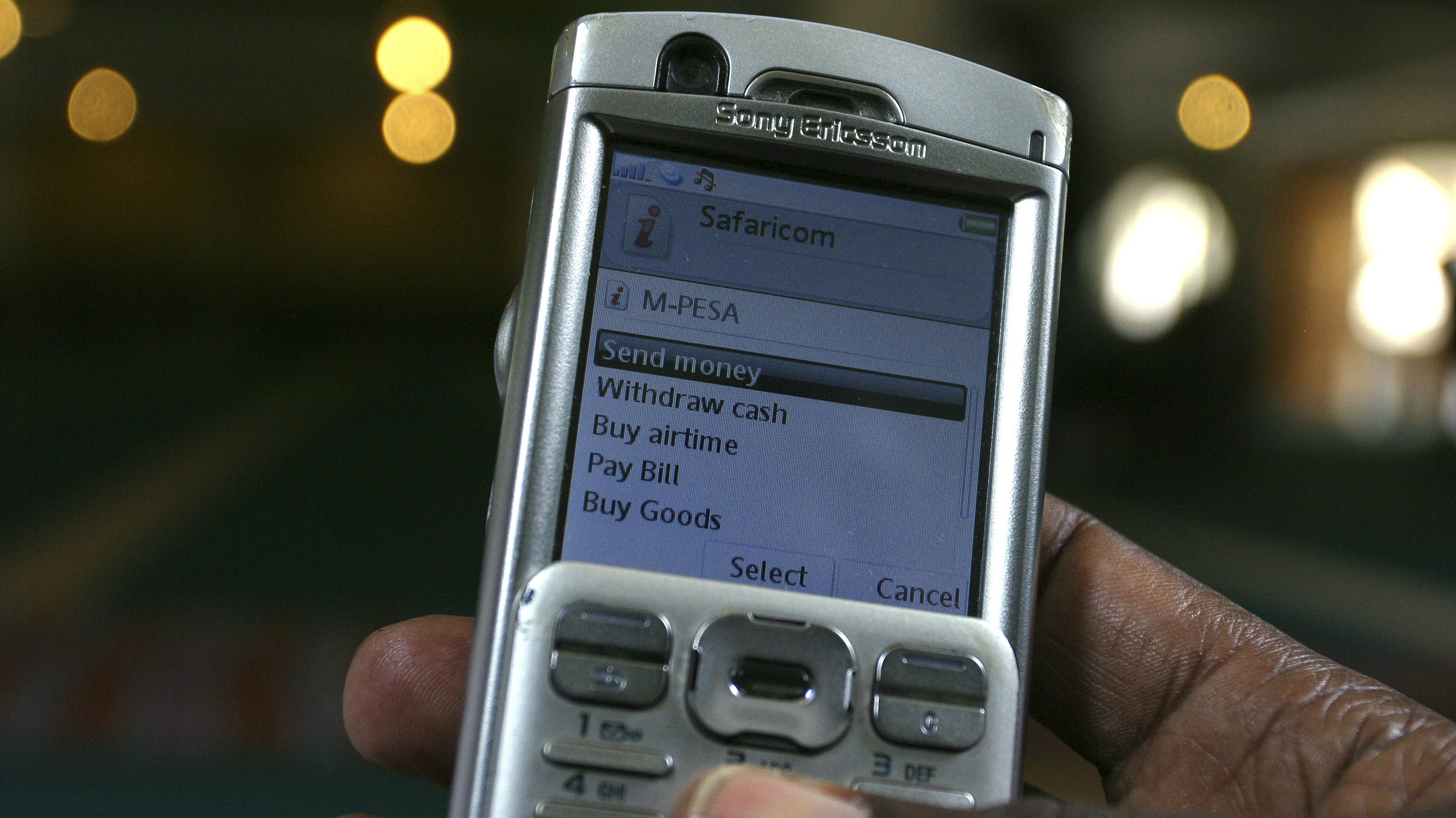 A man scrolls through his mobile phone to carry out a money transaction via M-PESA in Nairobi May 12, 2009.