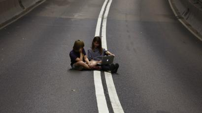 Two girls use a laptop computer on a vehicle passageway after pro-democracy protesters have blocked the traffic from going through at the financial Central district in Hong Kong early October 11, 2014.