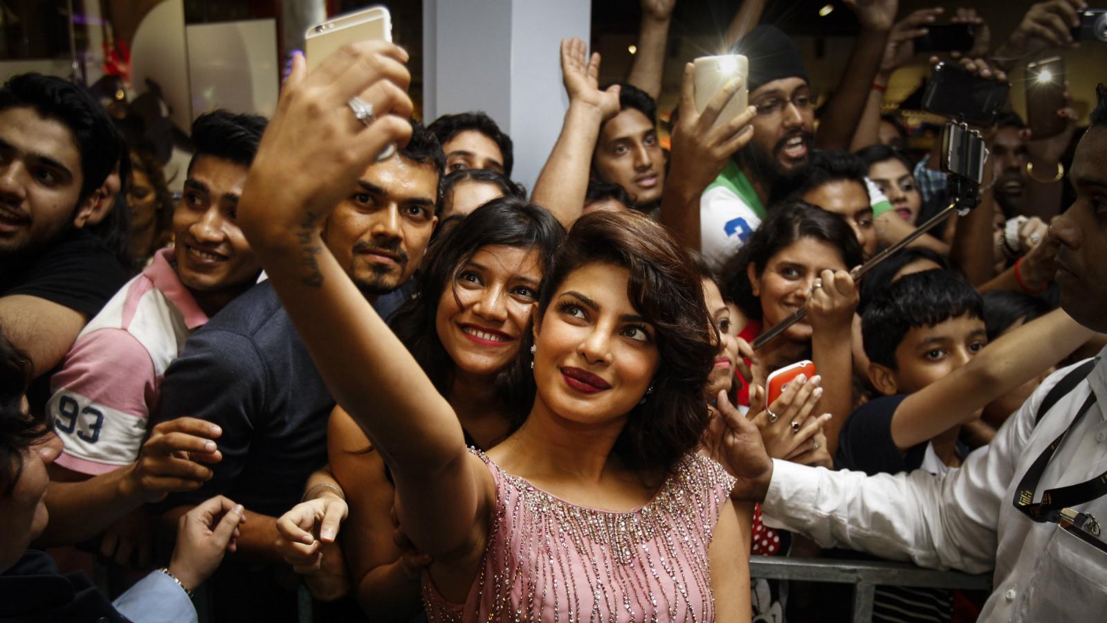 Bollywood actress Priyanka Chopra, center, has a selfie photo taken with fans during the IIFA Gala Screening as part of the three-day long International Indian Film Academy (IIFA) awards held in Kuala Lumpur, Malaysia, Saturday, June 6, 2015. The 16th IIFA is scheduled for June 5-7 in Malaysia. (AP Photo/Joshua Paul)