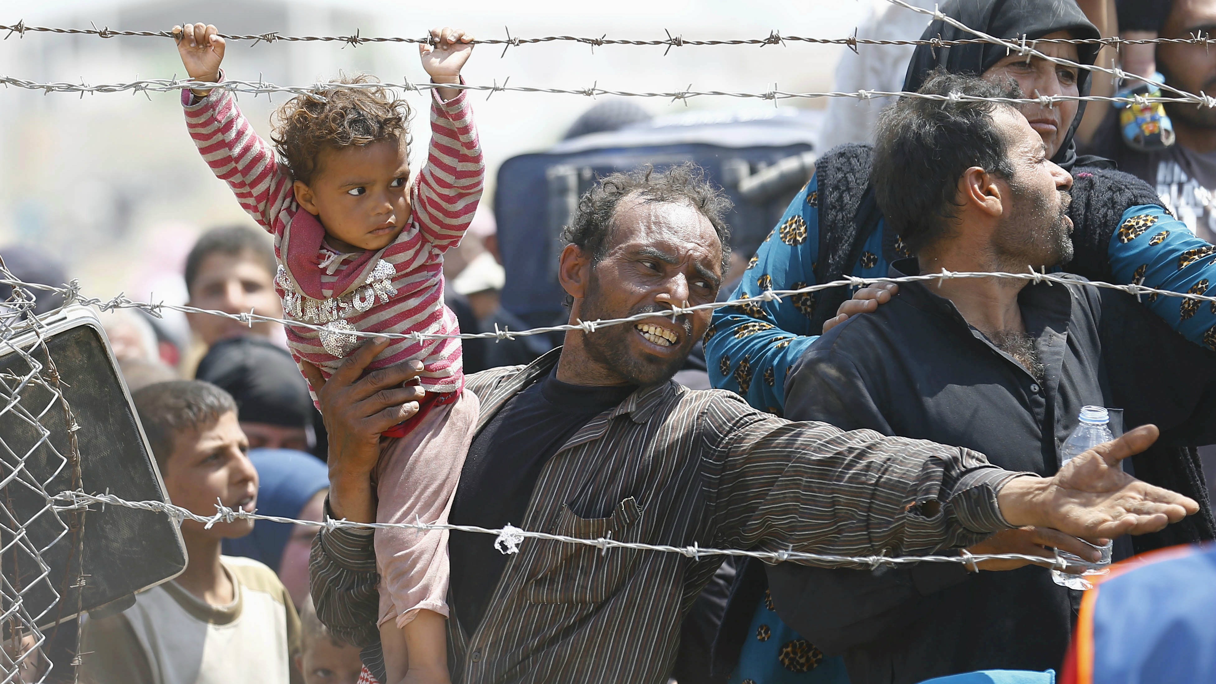 A Syrian refugee reacts as he waits behind border fences to cross into Turkey